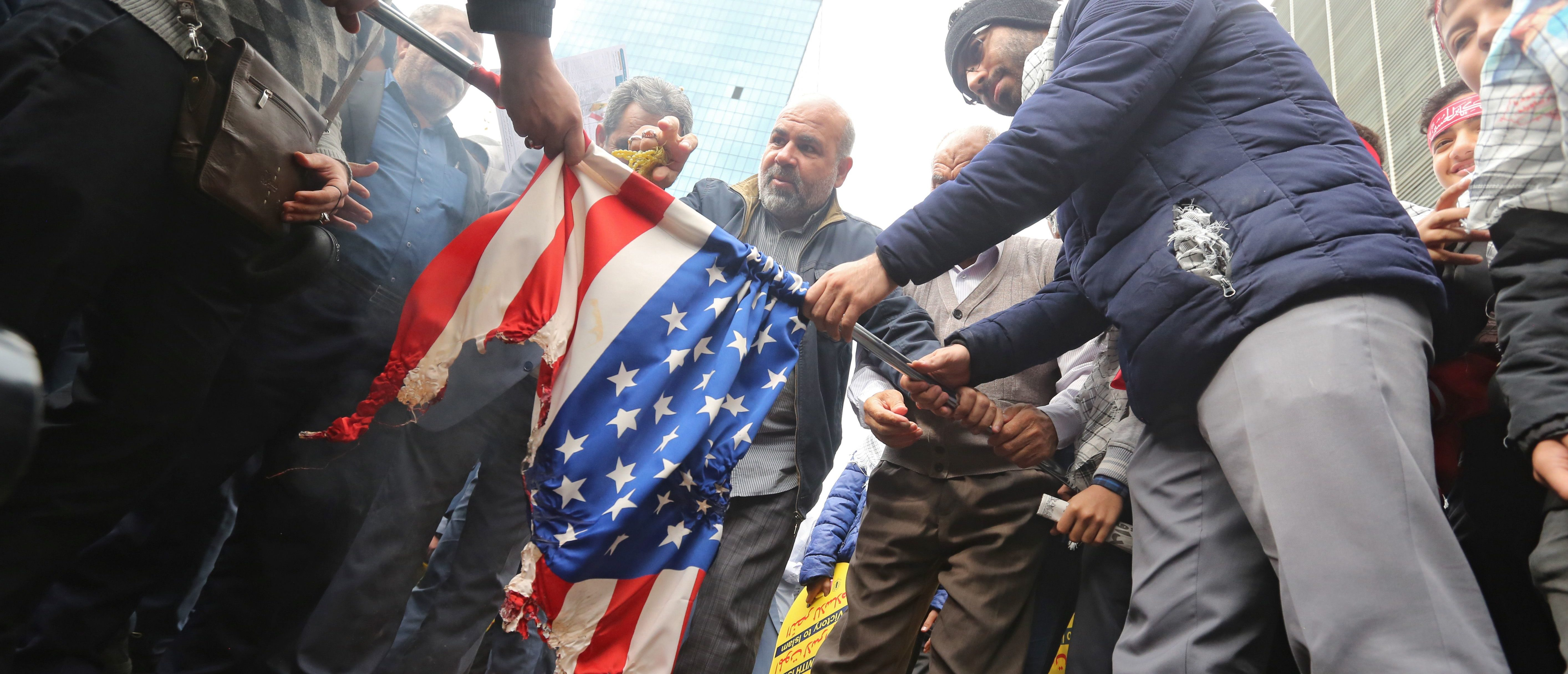 Iranian protesters set a US flag on fire during a rally outside the former US embassy in the Iranian capital Tehran on November 4, 2019, to mark the 40th anniversary of the Iran hostage crisis. (Photo by ATTA KENARE/AFP via Getty Images)