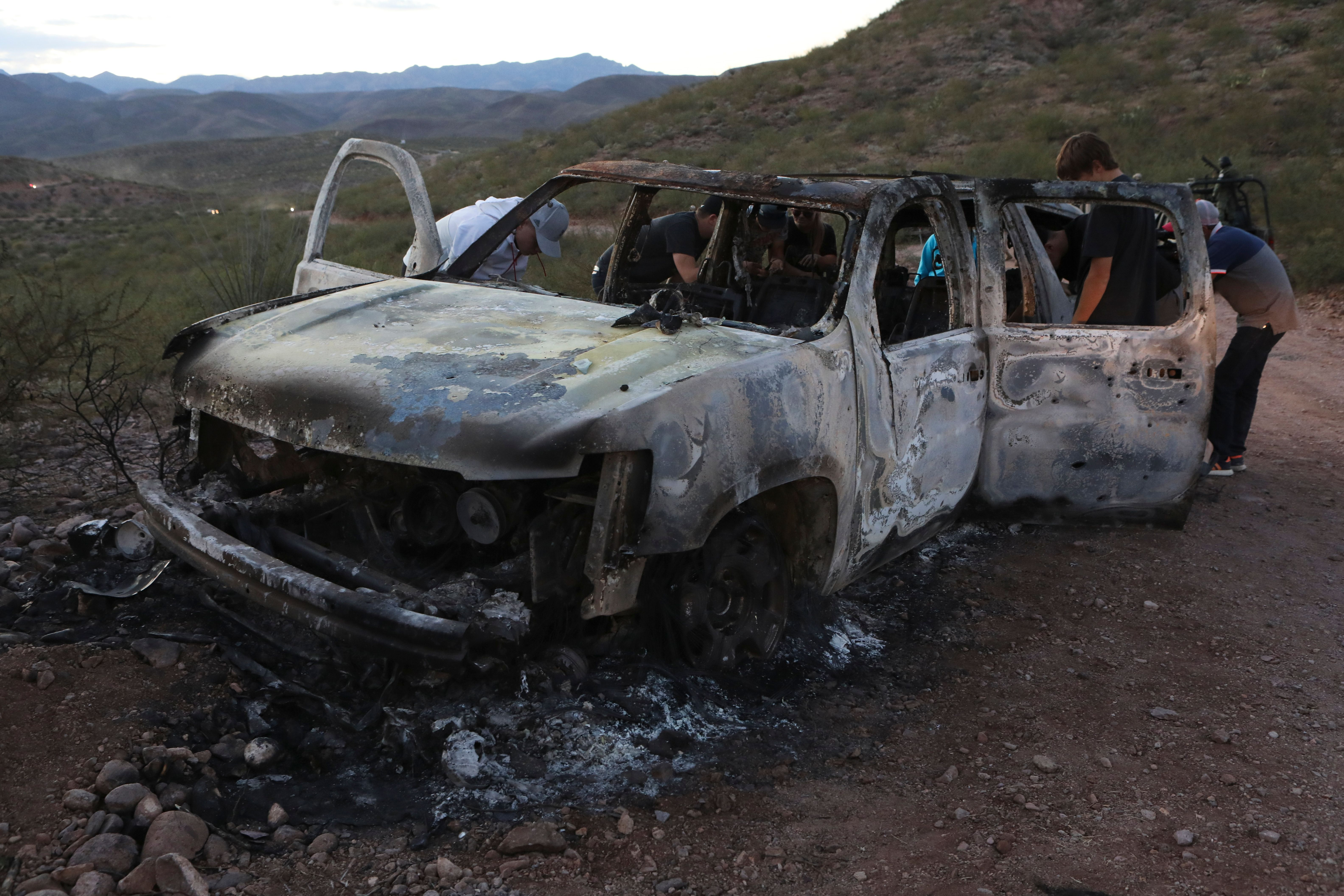 "Members of the Lebaron family watch the burned car where part of the nine murdered members of the family were killed and burned during an gunmen ambush on Bavispe, Sonora mountains, Mexico, on November 5, 2019. - US President Donald Trump offered Tuesday to help Mexico ""wage war"" on its cartels after three women and six children from an American Mormon community were murdered in an area notorious for drug traffickers. (Photo by Herika MARTINEZ / AFP) / The erroneous mention[s] appearing in the metadata of this photo by Herika MARTINEZ has been modified in AFP systems in the following manner: [AFP PHOTO / Herika MARTINEZ ] instead of [AFP PHOTO / STR ]. Please immediately remove the erroneous mention[s] from all your online services and delete it (them) from your servers. If you have been authorized by AFP to distribute it (them) to third parties, please ensure that the same actions are carried out by them. Failure to promptly comply with these instructions will entail liability on your part for any continued or post notification usage. Therefore we thank you very much for all your attention and prompt action. We are sorry for the inconvenience this notification may cause and remain at your disposal for any further information you may require. (Photo by HERIKA MARTINEZ/AFP via Getty Images)"