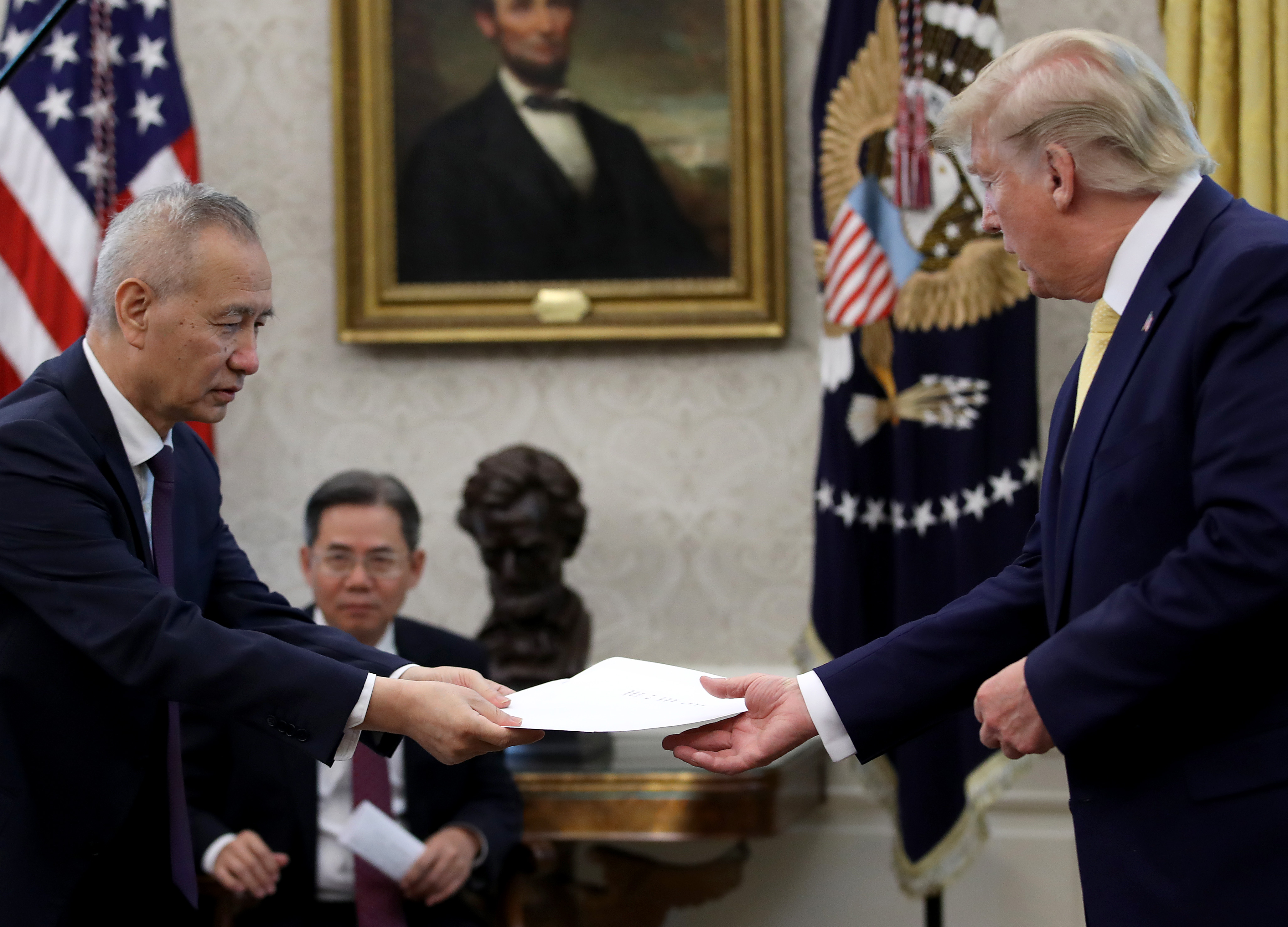 "Chinese Vice Premier Liu He presents U.S. President Donald Trump with a letter from Chinese President Xi Jinping after Trump announced a ""phase one"" trade agreement with China in the Oval Office at the White House October 11, 2019 in Washington, DC. (Photo by Win McNamee/Getty Images)"