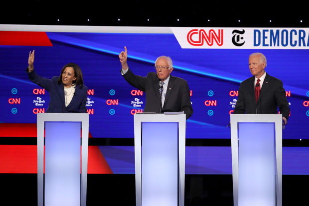 WESTERVILLE, OHIO - OCTOBER 15: Sen. Kamala Harris (D-CA) and Sen. Bernie Sanders (I-VT) raise their hands as former Vice President Joe Biden look on during the Democratic Presidential Debate at Otterbein University on October 15, 2019 in Westerville, Ohio. A record 12 presidential hopefuls are participating in the debate hosted by CNN and The New York Times. (Photo by Win McNamee/Getty Images)