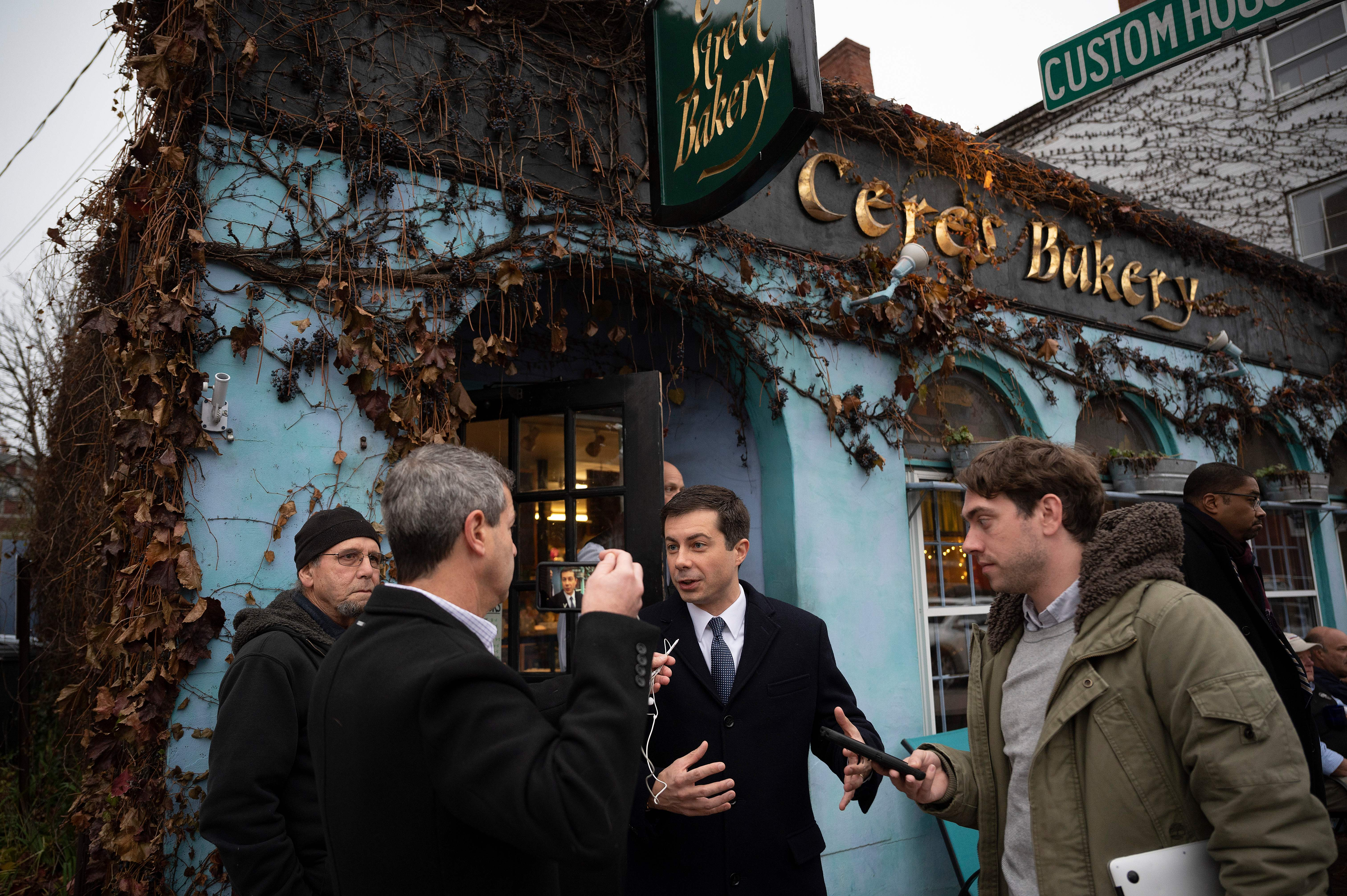 Democratic presidential hopeful Mayor Pete Buttigieg (C) speaks with a reporter as he departs Ceres Bakery in in Portsmouth, New Hampshire, on November 11, 2019, as he continues his 4-day bus tour of the state. - Pete Buttigieg is criss-crossing New Hampshire on a mission: to convince voters that a 30-something smalltown mayor with an unapologetically moderate message is the Democratic Party's best shot at ousting President Donald Trump. (Photo by JIM WATSON / AFP) (Photo by JIM WATSON/AFP via Getty Images)