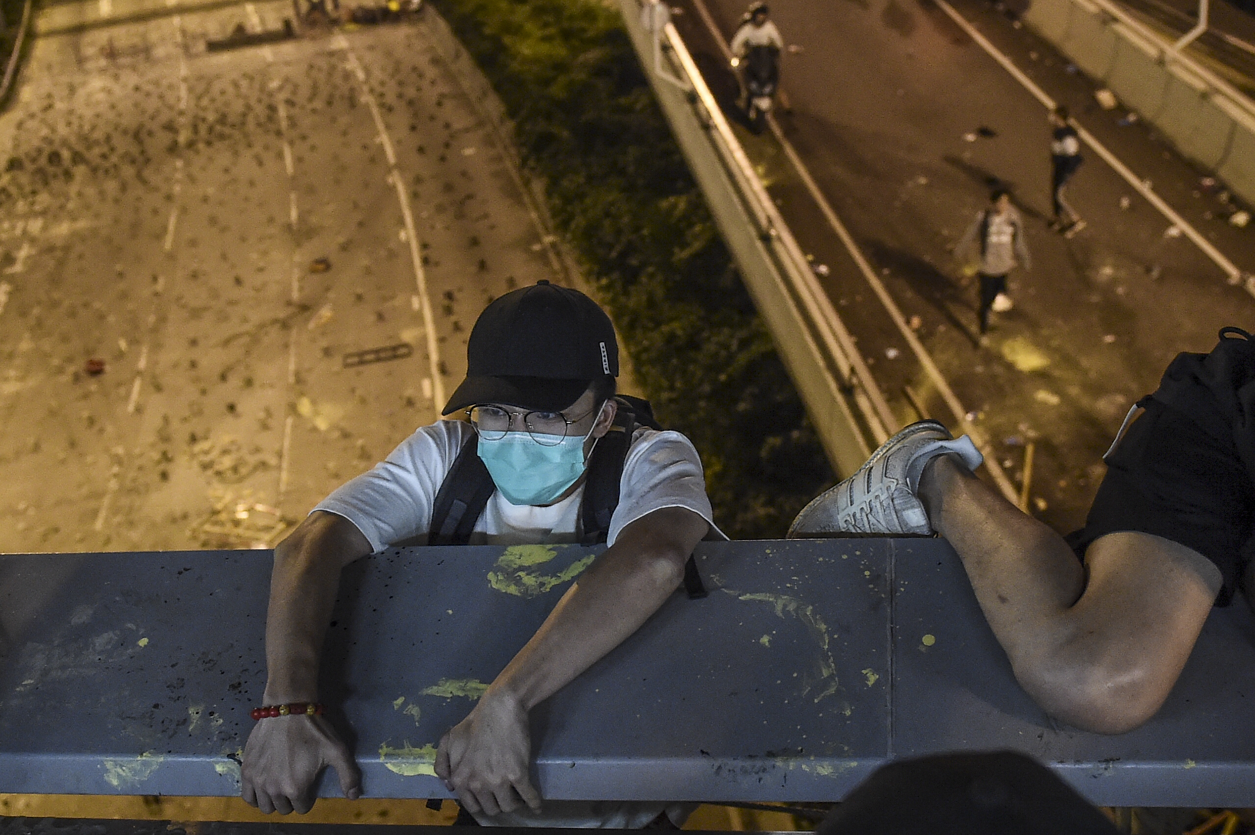 A protester lowers himself down from a bridge to a highway, to escape from Hong Kong Polytechnic University campus and from police, in Hung Hom district in Hong Kong on November 18, 2019. (YE AUNG THU/AFP via Getty Images)