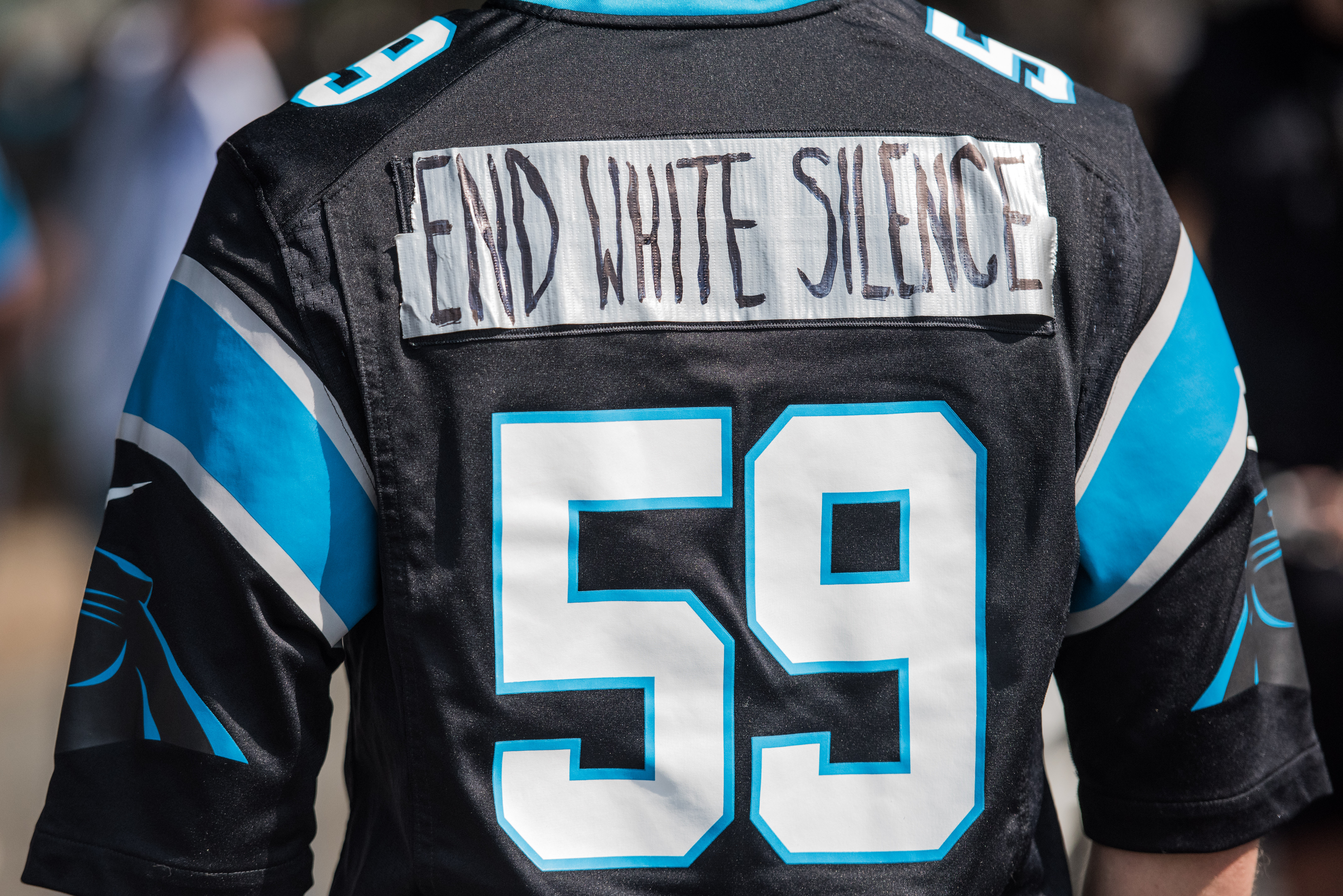 CHARLOTTE, NC - SEPTEMBER 25: A demonstrator wears a Carolina Panthers jersey outside of Bank of America Stadium before an NFL football game between the Charlotte Panthers and the Minnesota Vikings September 25, 2016 in Charlotte, NC. Protests have disrupted the city since Tuesday night following the shooting of 43-year-old Keith Lamont Scott at an apartment complex near UNC Charlotte. (Photo by Sean Rayford/Getty Images)