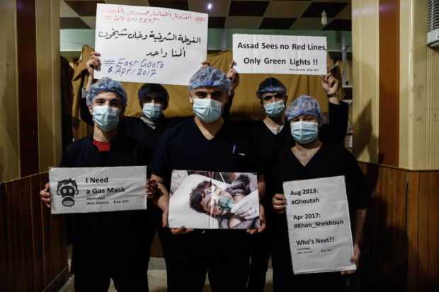 "TOPSHOT - Medical staff at Damascus Countryside Specialised Hospital hold placards condemning a suspected chemical weapons attack on the Syrian town of Khan Sheikhun, during a gathering to show solidarity with the victims in the rebel-held Douma on the outskirts of Damascus on April 6, 2017. US forces fired a barrage of cruise missiles at a Syrian airbase on April 7 in response to what President Donald Trump called a ""barbaric"" chemical attack he blamed on the Damascus regime. Syria's regime has denied any use of chemical weapons and state media on Friday described the US strike -- which was reported to have pulverised the base and killed at least four servicemen -- as an ""act of aggression"". / AFP PHOTO / Sameer Al-Doumy (Photo credit should read SAMEER AL-DOUMY/AFP via Getty Images)"