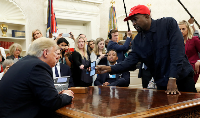 Rapper Kanye West shows President Donald Trump a picture on his mobile phone of what he described as a hydrogen powered airplane that should replace Air Force One during a meeting in the Oval Office at the White House in Washington, U.S., October 11, 2018. REUTERS/Kevin Lamarque