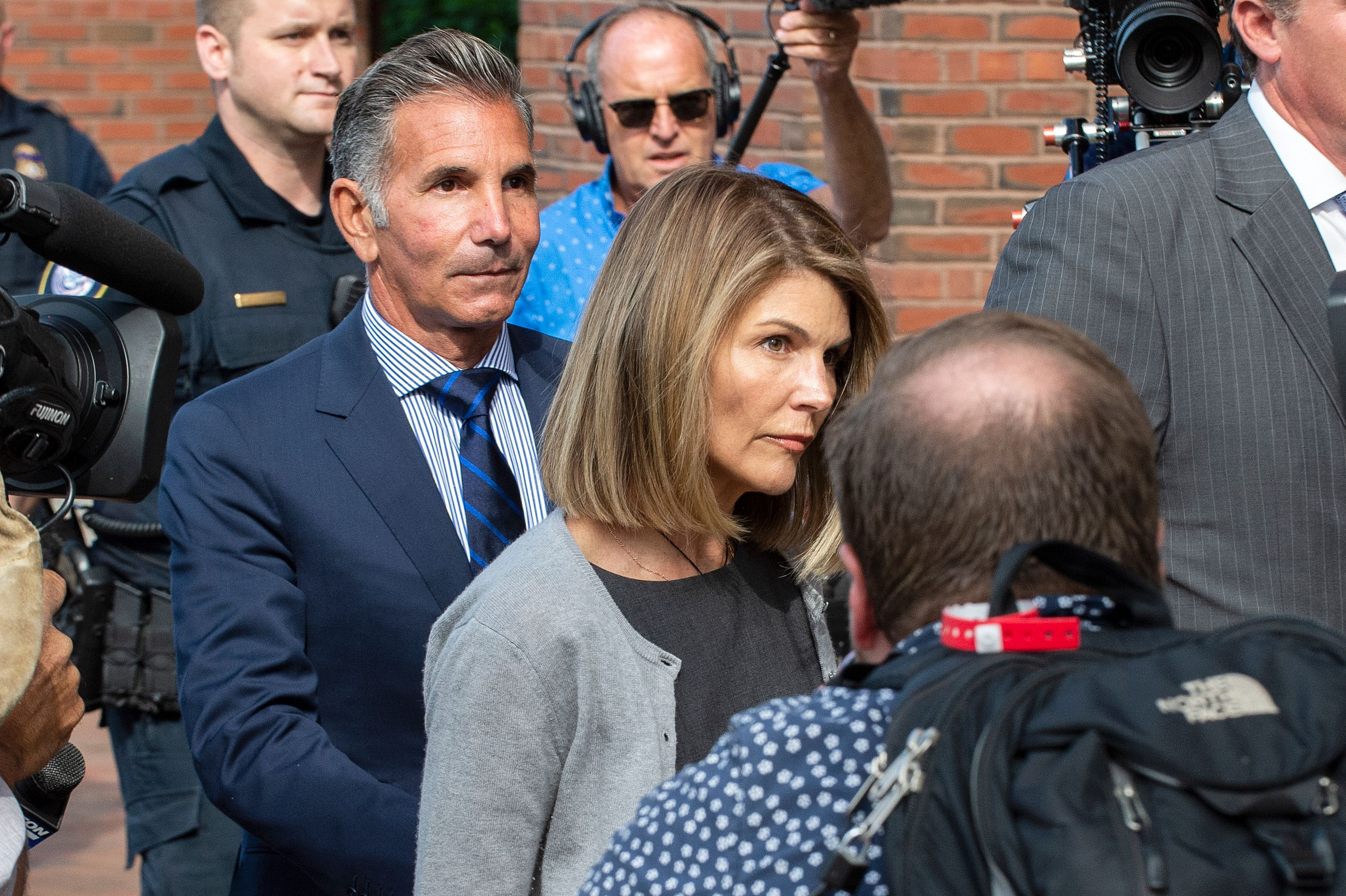 Actress Lori Loughlin and husband Mossimo Giannulli exit the Boston Federal Court house after a pre-trial hearing with Magistrate Judge Kelley at the John Joseph Moakley US Courthouse in Boston on August 27, 2019. - Loughlin and Giannulli are charged with conspiracy to commit mail and wire fraud and conspiracy to commit money laundering in the college admissions scandal. (Photo credit JOSEPH PREZIOSO/AFP via Getty Images)