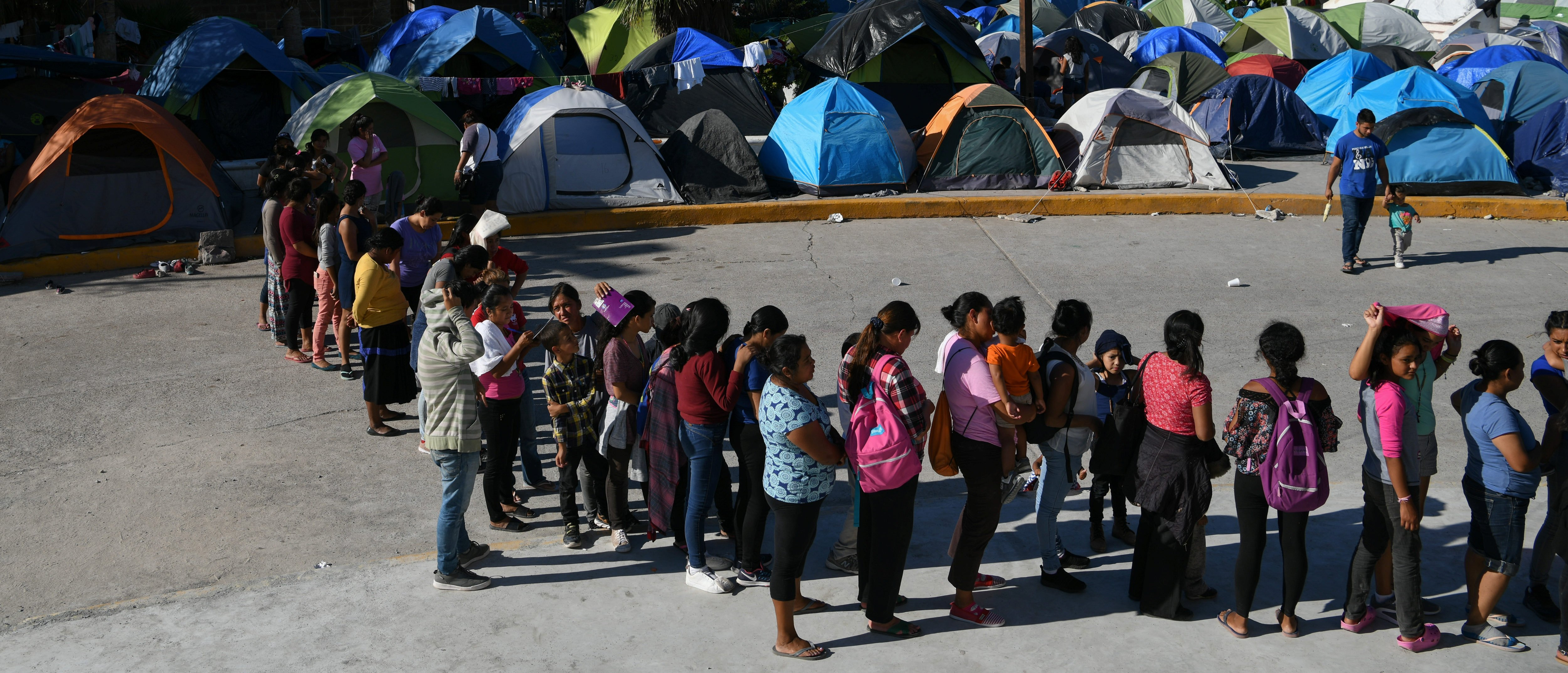 "Migrants, most of them asylum seekers sent back to Mexico from the U.S. under the ""Remain in Mexico"" program, officially named Migrant Protection Protocols (MPP), wait in line for a meal outside the Human Repatriation office in Matamoros"