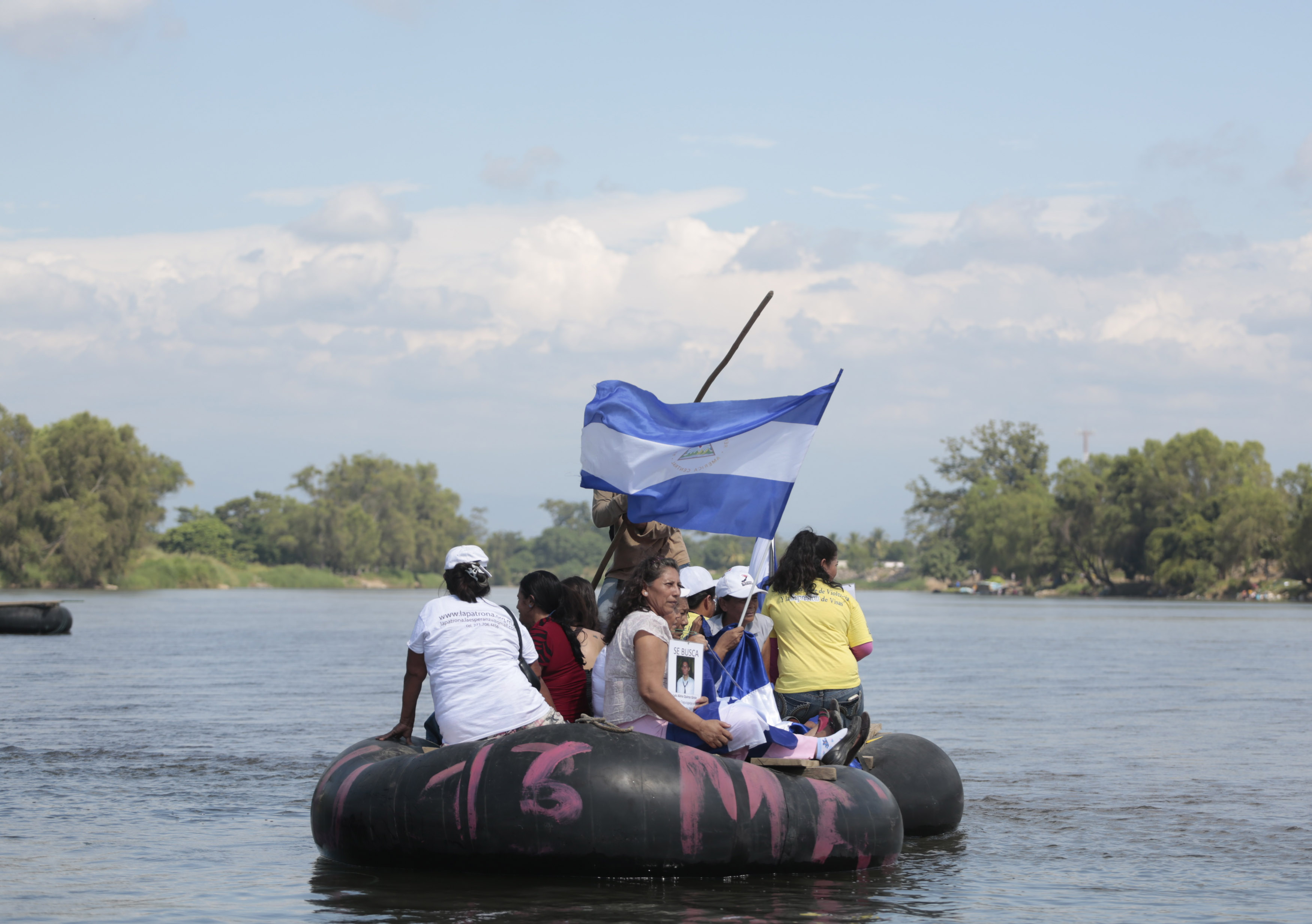 """Women from """"Caravana de Madres Centroamericanas"""" displays photos of missing migrants and a Salvadorian flag as they ride a raft to cross to Guatemala from the Suchiate river in the border of Ciudad Hidalgo"""