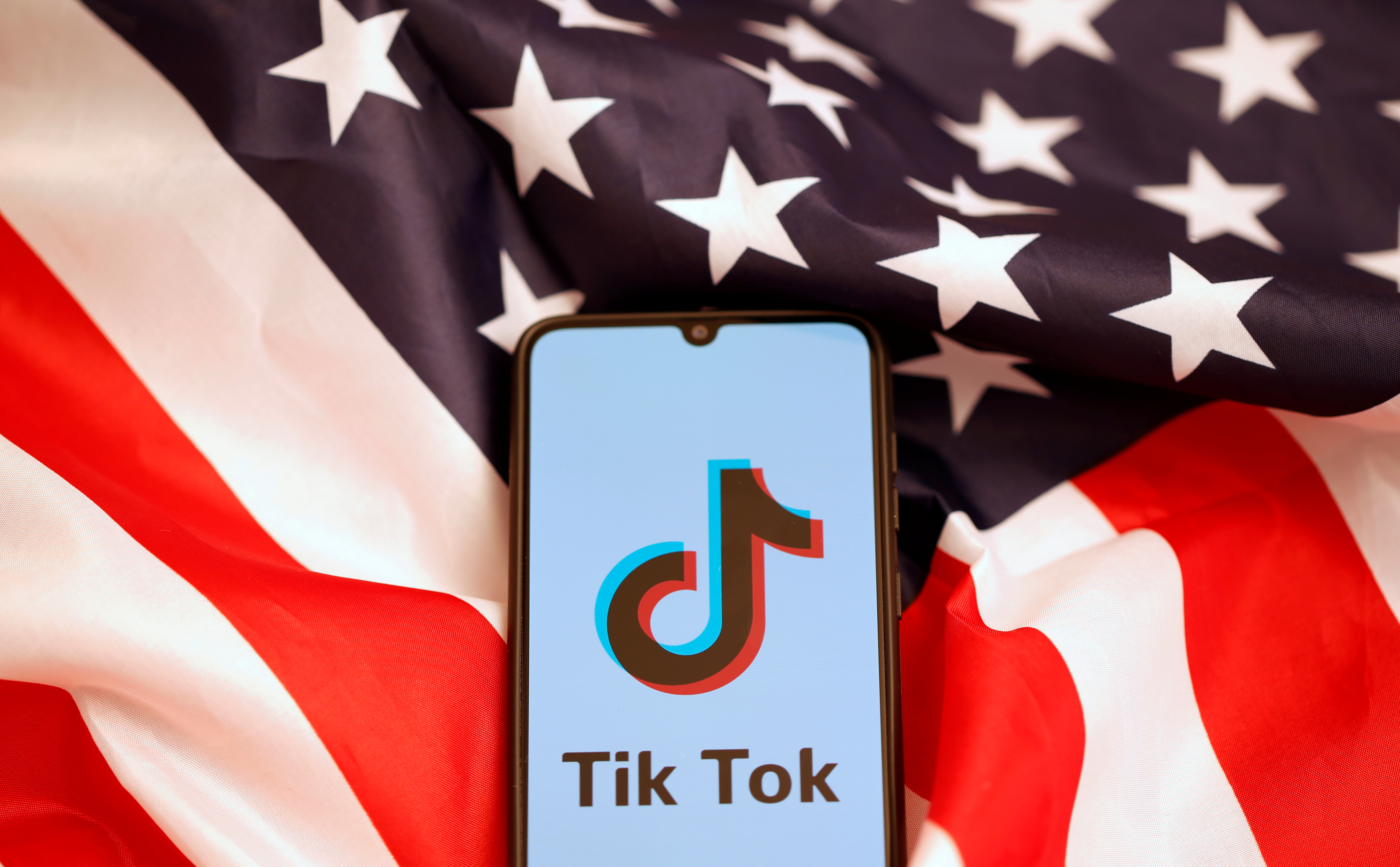 Tik Tok logo is displayed on the smartphone while standing on the U.S. flag in this illustration picture taken, November 8, 2019. REUTERS/Dado Ruvic - RC277D9TA8TQ