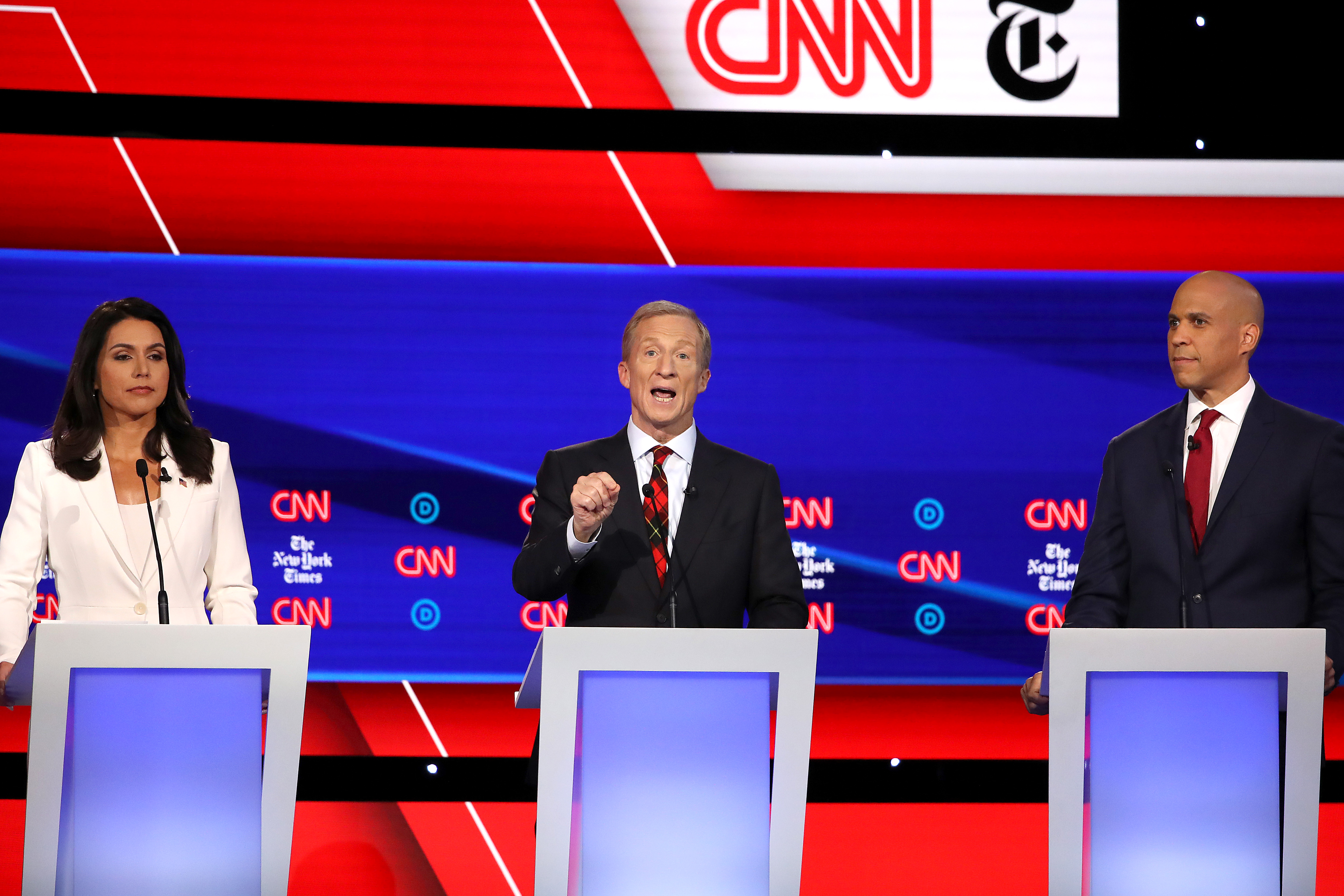 WESTERVILLE, OHIO - OCTOBER 15: Billionaire Tom Steyer (C) speaks as Rep. Tulsi Gabbard (D-HI) and Sen. Cory Booker (D-NJ) look on during the Democratic Presidential Debate at Otterbein University on October 15, 2019 in Westerville, Ohio (Win McNamee/Getty Images)