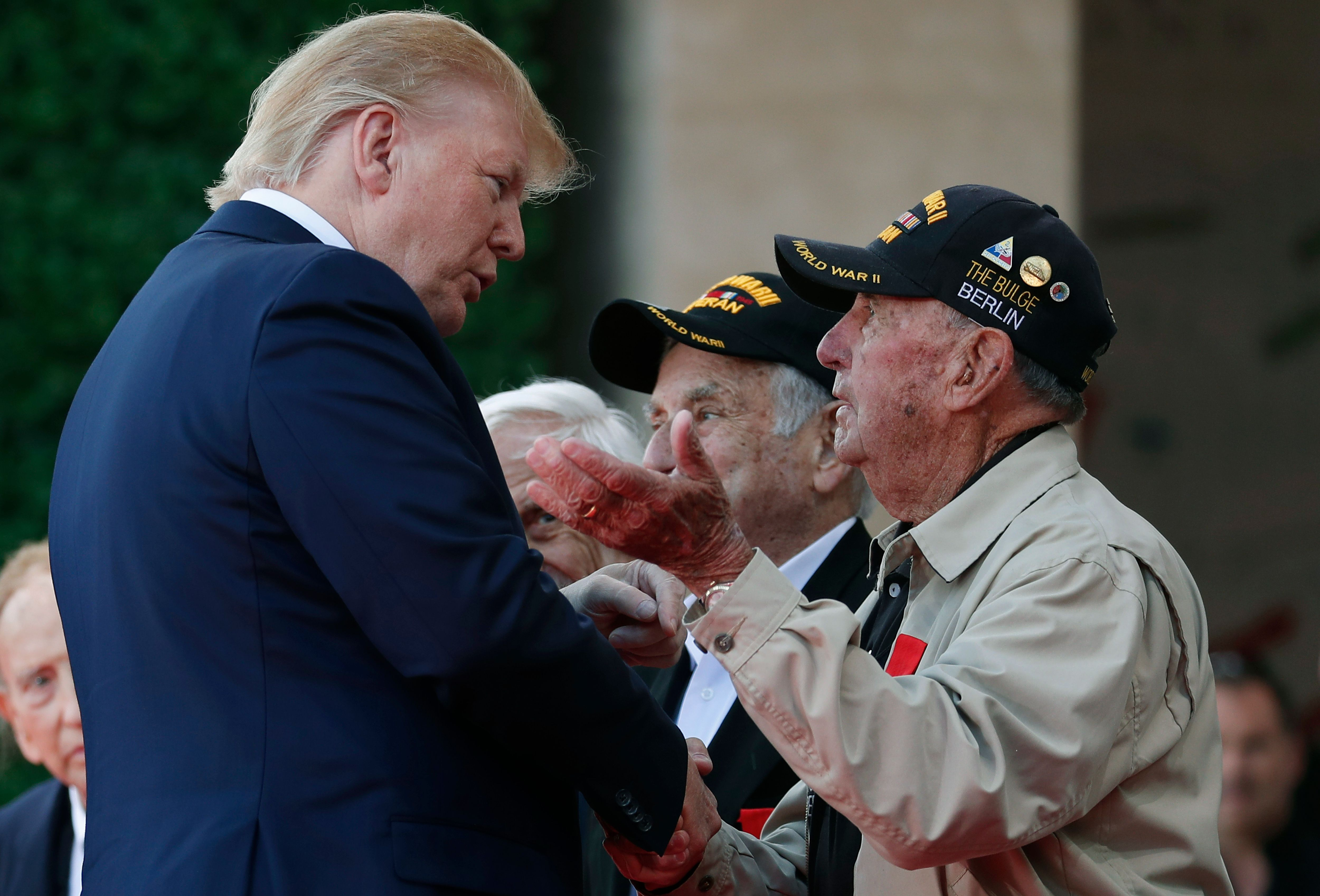US President Donald Trump (C) greets an US veteran during a French-US ceremony at the Normandy American Cemetery and Memorial in Colleville-sur-Mer, Normandy, northwestern France, on June 6, 2019, as part of D-Day commemorations marking the 75th anniversary of the World War II Allied landings in Normandy. (IAN LANGSDON/AFP via Getty Images)