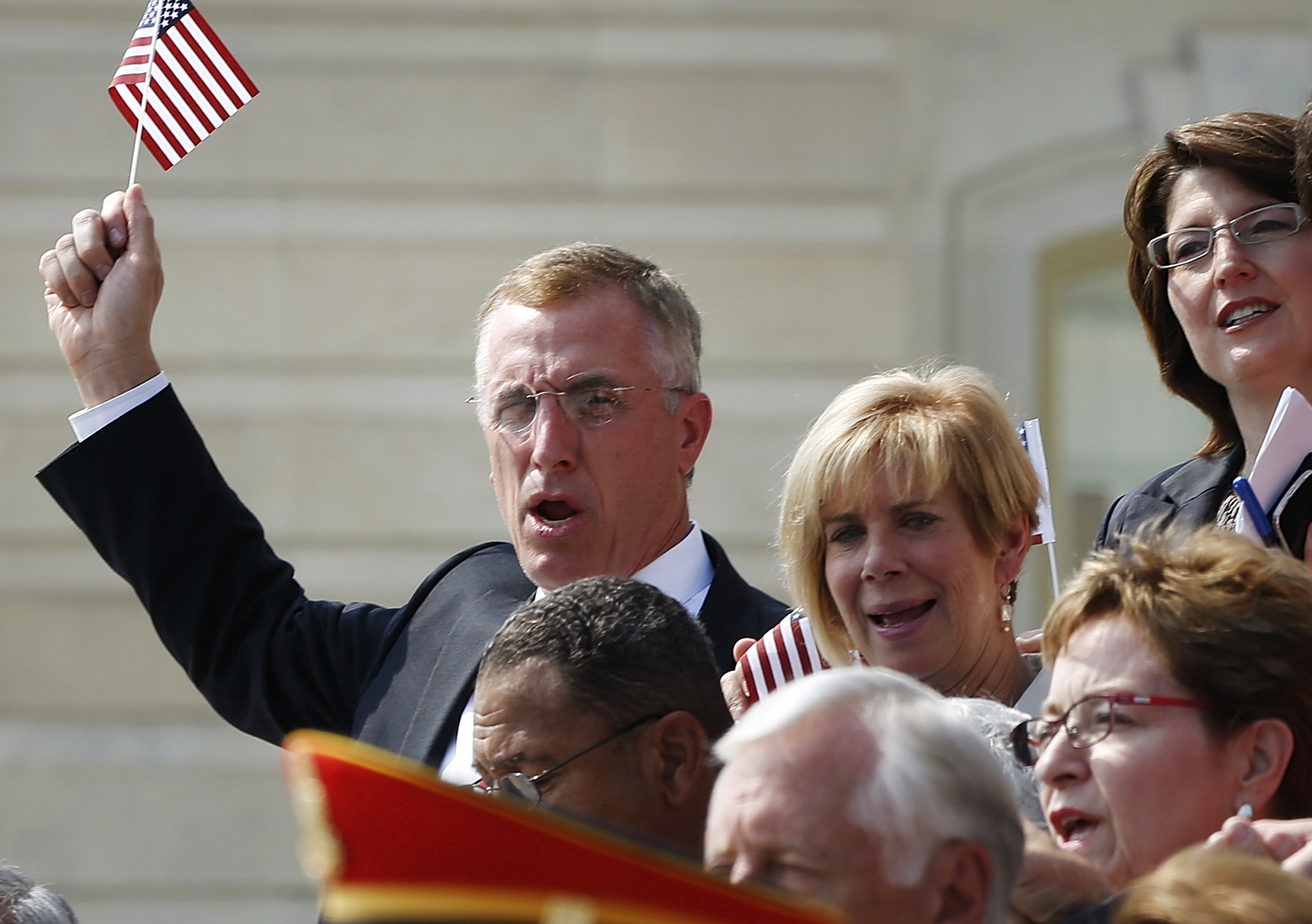 """U.S. Representative Tim Murphy (R-PA) holds up a U.S. flag as he and other members of the U.S. Congress sing """"God Bless America"""" in remembrance of lives lost in the 9/11 attacks, on the steps of the U.S. Capitol in Washington, September 11, 2013. Bagpipes, bells and a reading of the names of the nearly 3,000 people killed when hijacked jetliners crashed into the World Trade Center, the Pentagon and a Pennsylvania field marked the 12th anniversary of the September 11 attacks in 2001. REUTERS/Jonathan Ernst (UNITED STATES - Tags: POLITICS ANNIVERSARY DISASTER) - GM1E99C03BU01"""