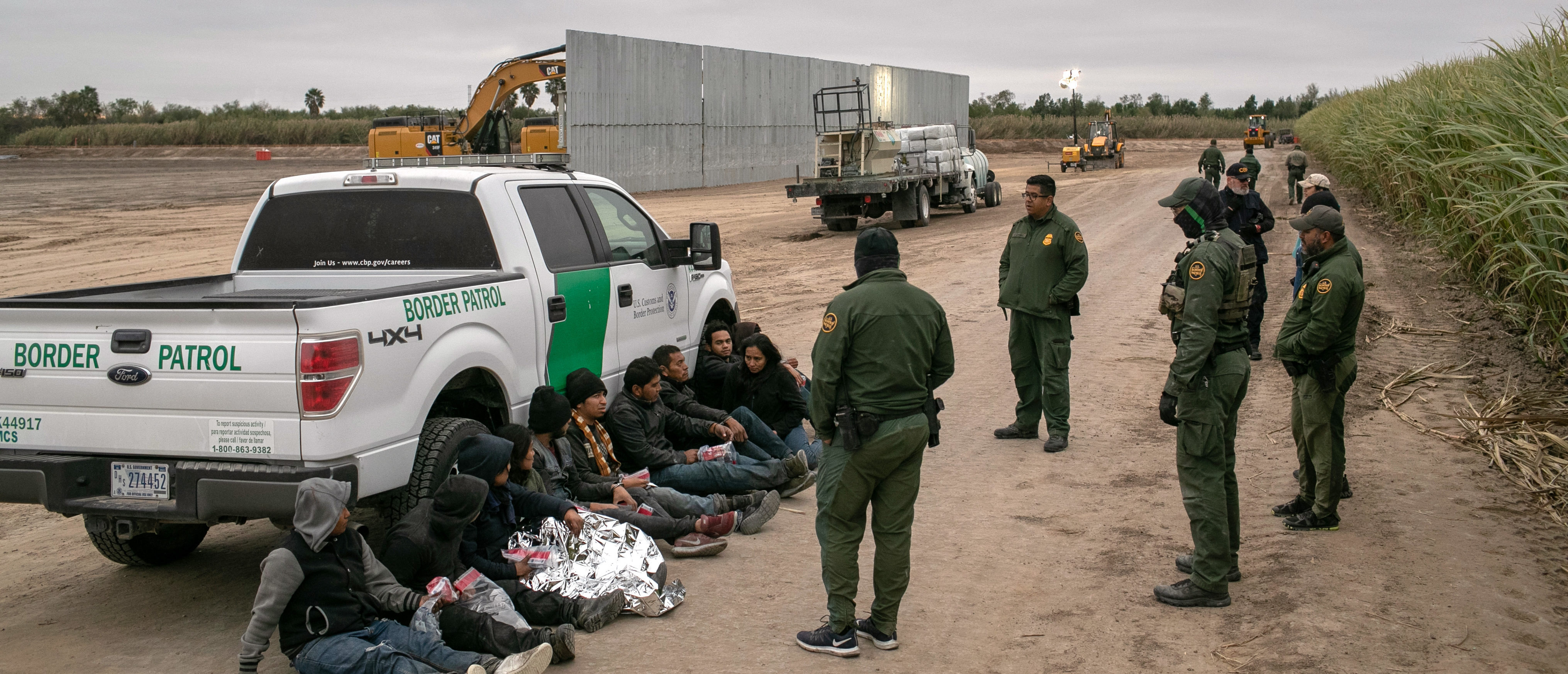 U.S. Border Patrol agents detain undocumented immigrants caught near a section of privately-built border wall under construction on Dec. 11, 2019 near Mission, Texas. (Photo by John Moore/Getty Images)