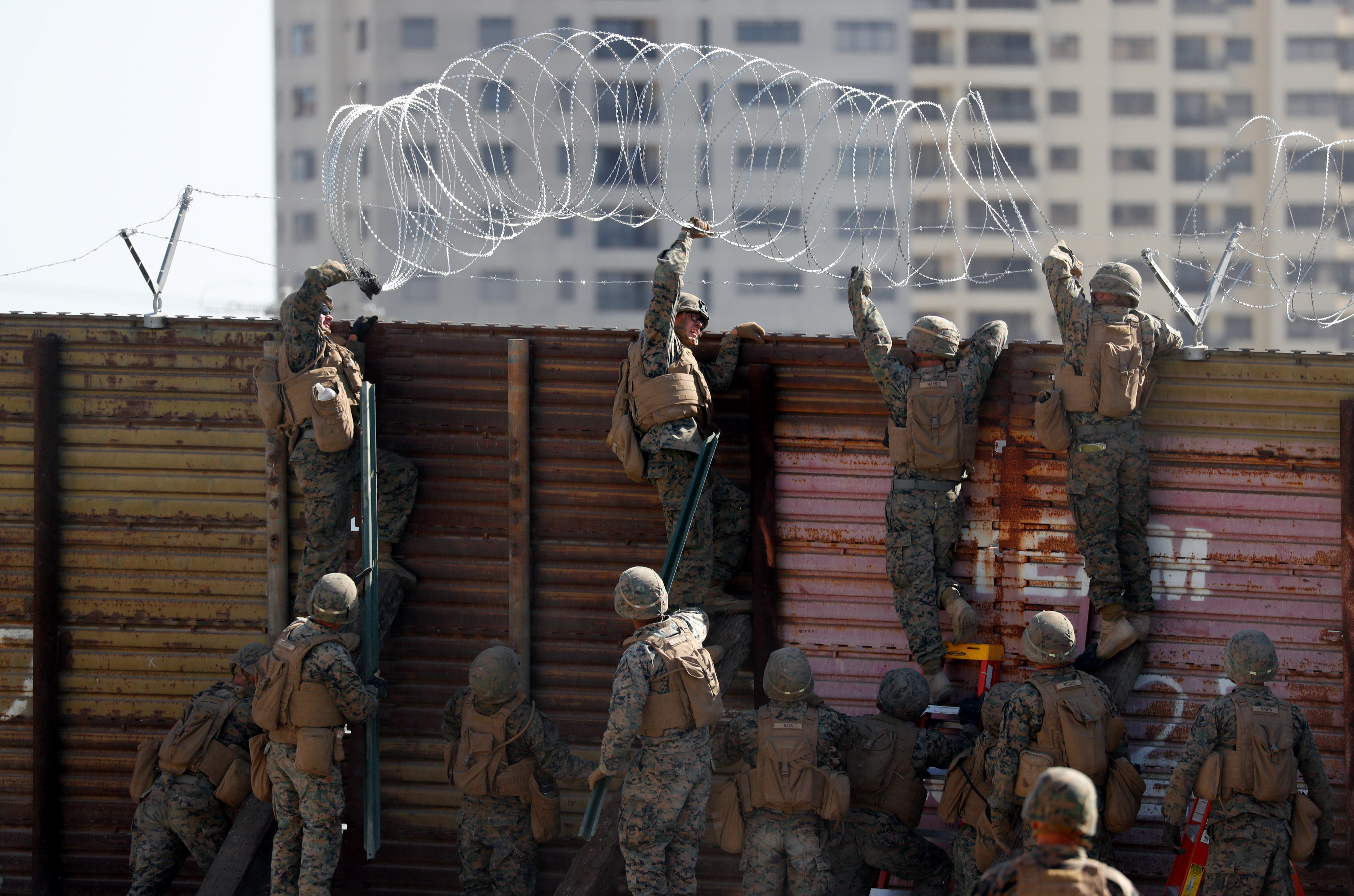 U.S. Marines instal concertina wire along the top of the primary border wall at the port of entry next to Tijuana in San Ysidro
