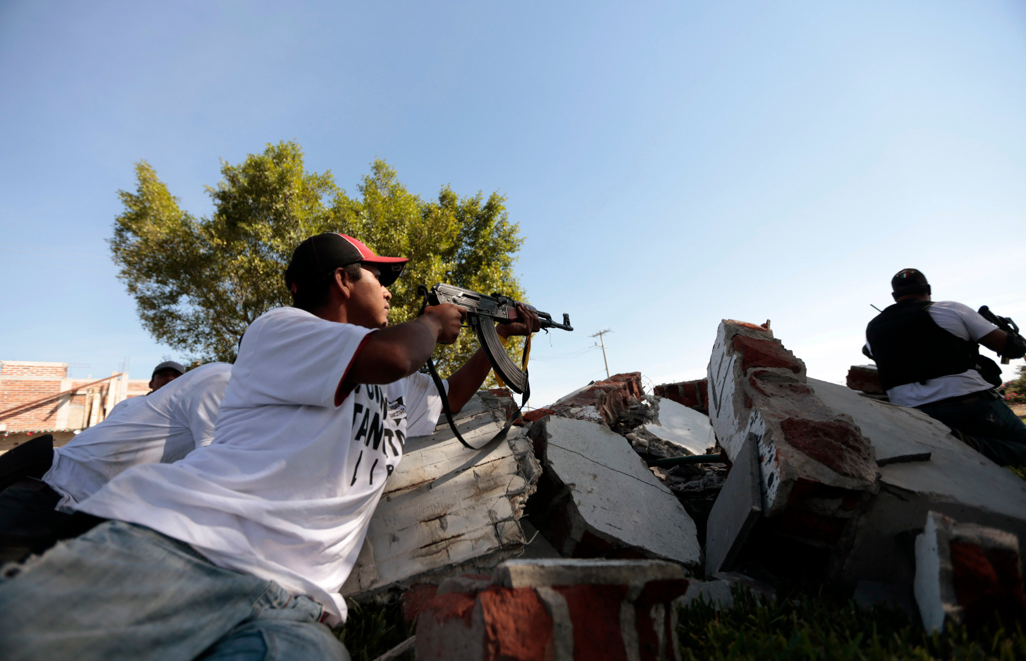 Vigilante member of the community police aims his weapon after entering the village of Paracuaro in Michoacan state