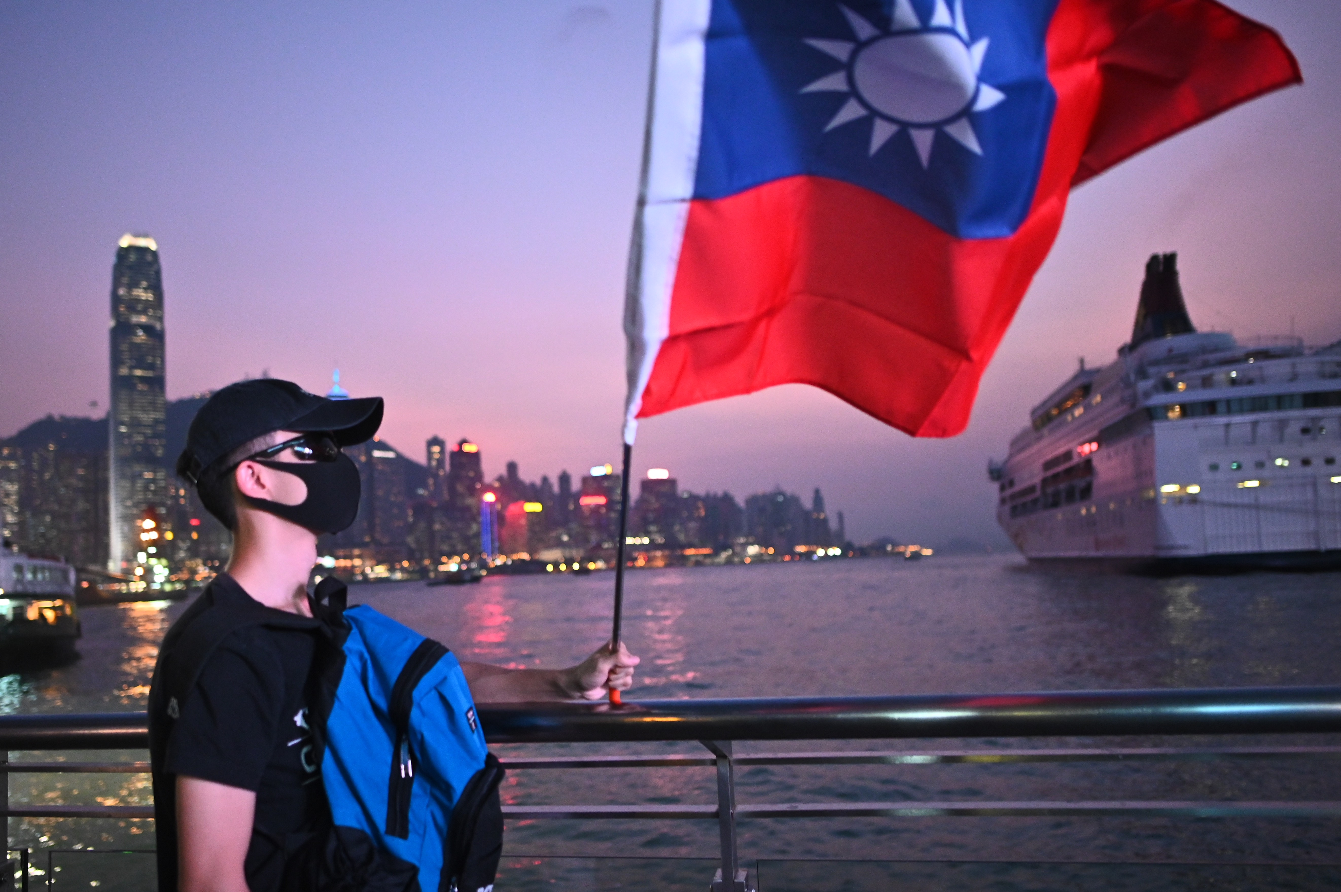 A man wearing a mask holds a Taiwanese flag as he joins others at a rally to mark Taiwan's National Day, in the Tsim Sha Tsui district in Hong Kong on October 10, 2019. - Taiwan's National Day, also called called Double-Ten in a reference to the nationalist Republic of China set up by Sun Yat Sen on October 10, 1911, ending centuries of Chinese dynastic rule. (Photo by Philip FONG / AFP) (Photo by PHILIP FONG/AFP via Getty Images)