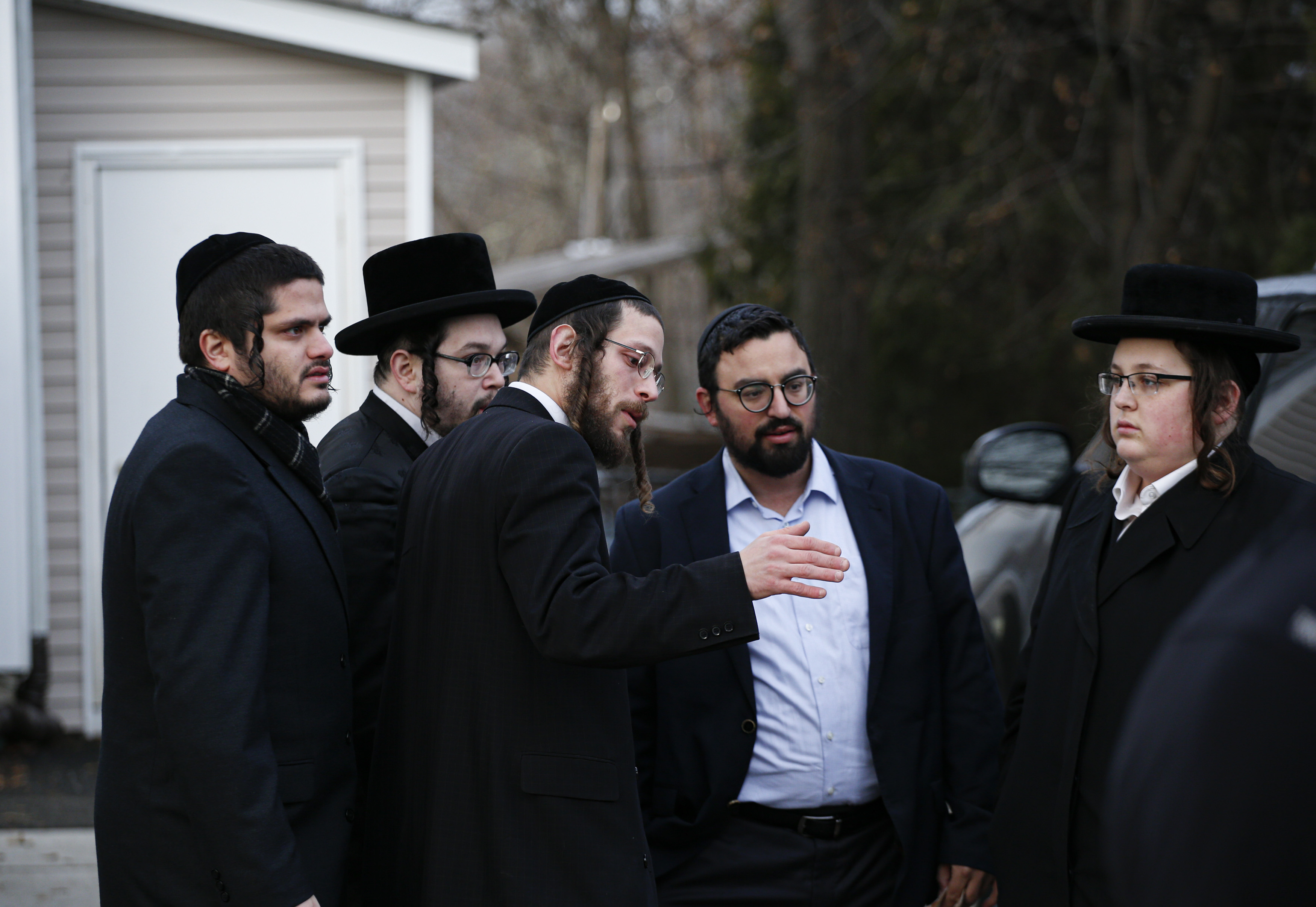 Members of the Jewish community gather outside the home of rabbi Chaim Rottenbergin Monsey, in New York on December 29, 2019 after a machete attack that took place earlier outside the rabbi's home during the Jewish festival of Hanukkah in Monsey, New York. - An intruder stabbed and wounded five people at a rabbi's house in New York during a gathering to celebrate the Jewish festival of Hanukkah late on December 28, 2019, officials and media reports said. Local police departments, speaking to AFP, declined to give the number of people injured, but a suspect has been taken into custody and a vehicle safeguarded, an NYPD spokesman said. (Photo by KENA BETANCUR/AFP via Getty Images)