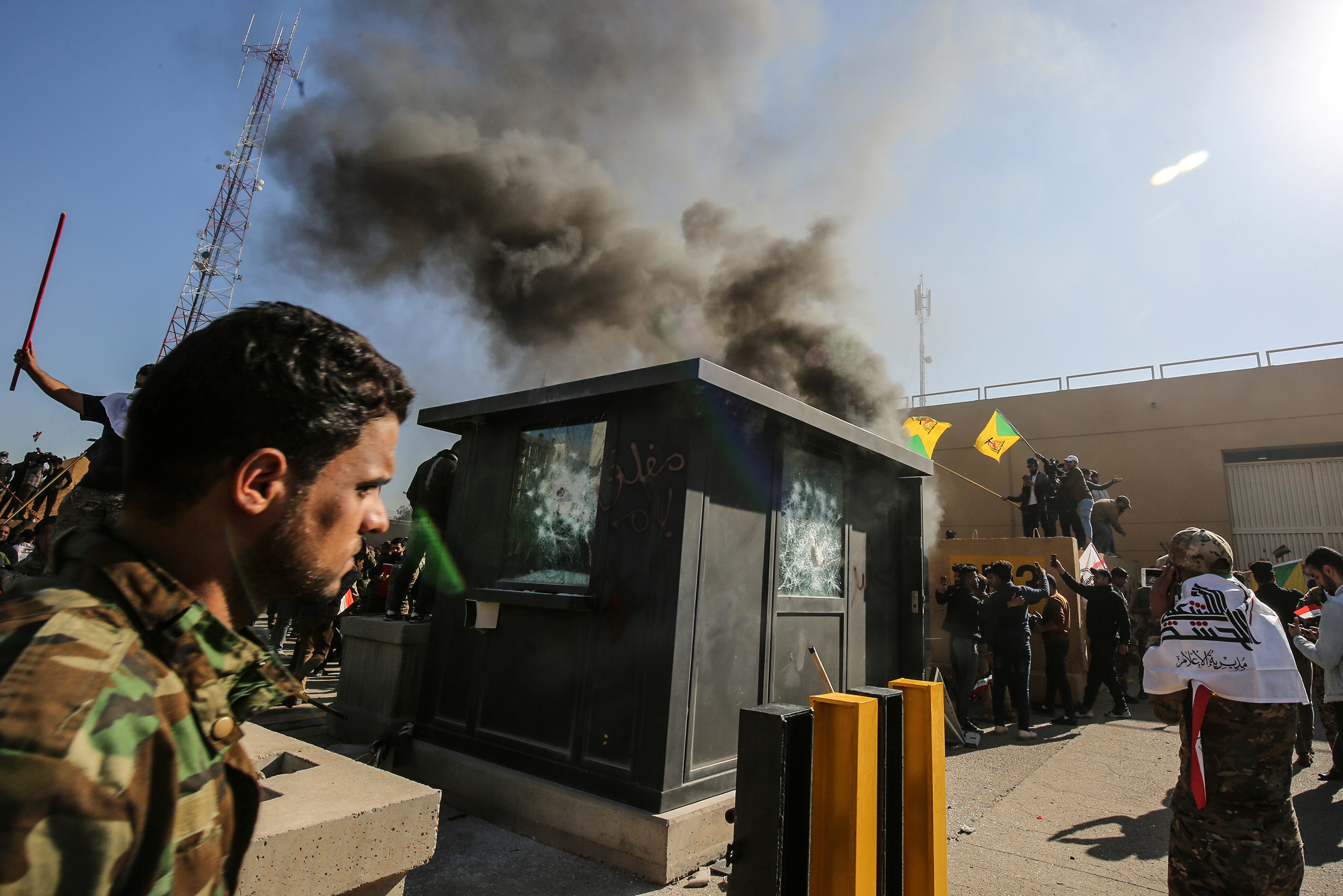 Members of the Iraqi pro-Iranian Hashed al-Shaabi group and protesters set ablaze a sentry box in front of the US embassy building in the capital Baghdad to protest against the weekend's air strikes. (AHMAD AL-RUBAYE/AFP via Getty Images)