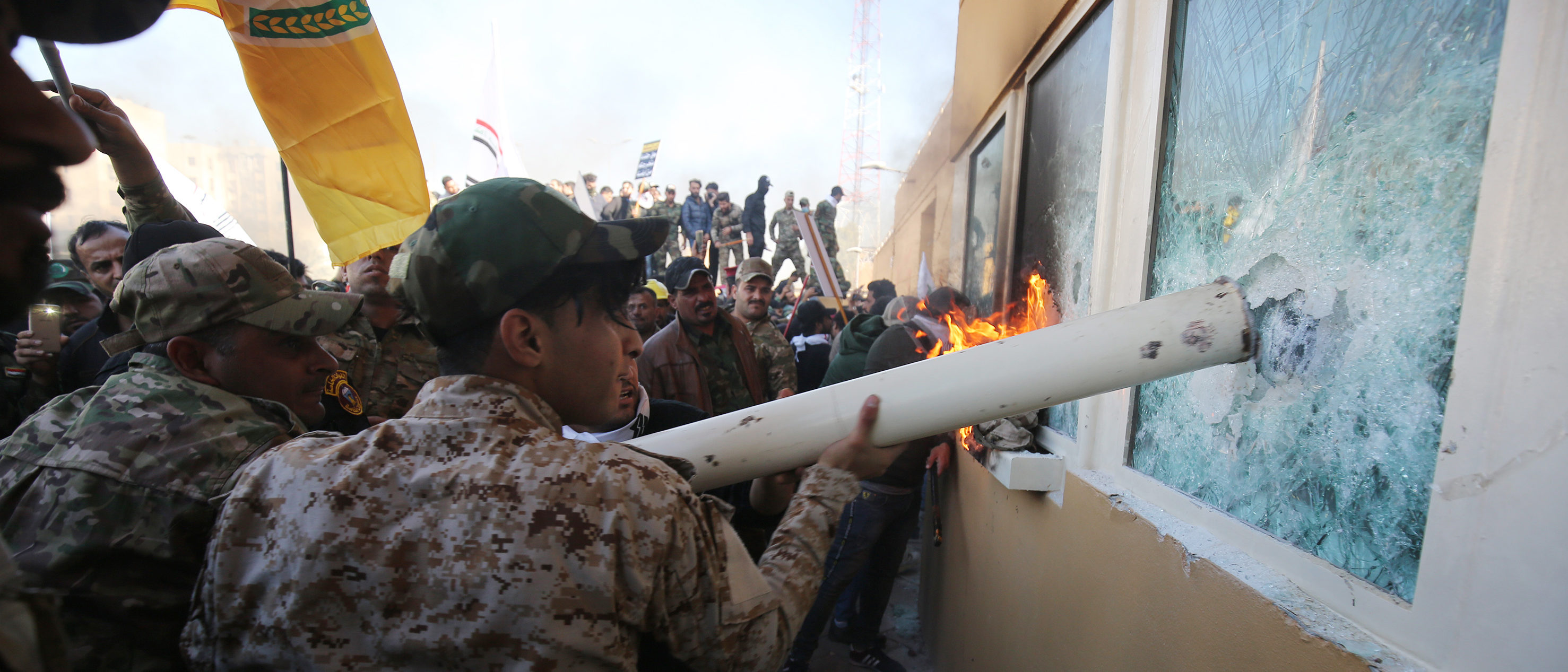 Iraqi protesters use a plumbing pipe to break the bullet-proof glass of the US embassy's windows in Baghdad, as thousands of angry Iraqis, including members the Hashed al-Shaabi breached the outer wall of the diplomatic mission on December 31, 2019. (AHMAD AL-RUBAYE/AFP via Getty Images)