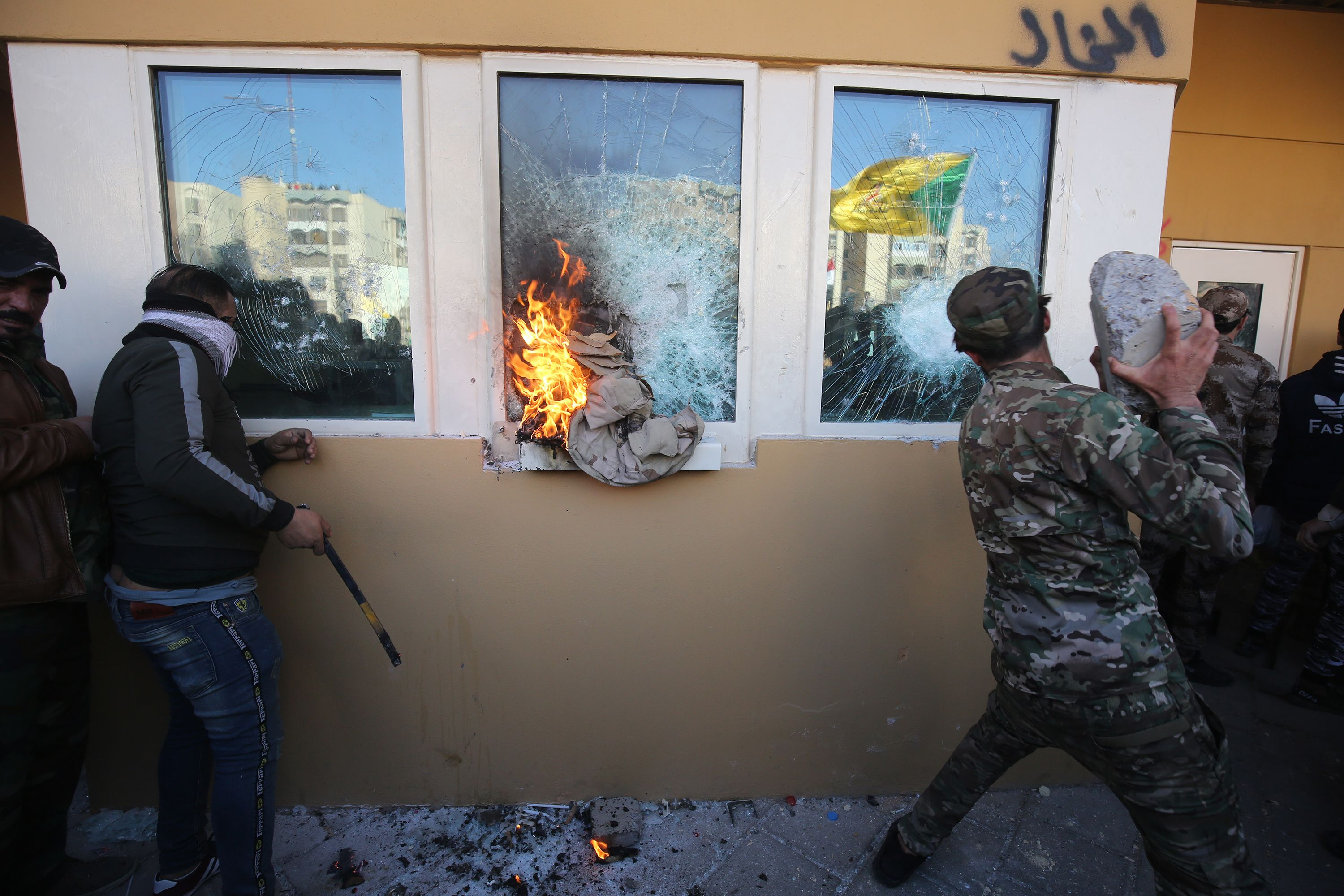 Members the Hashed al-Shaabi, a mostly Shiite network of local armed groups trained and armed by powerful neighbour Iran, smash the bullet-proof glass of the US embassy's windows in Baghdad with blocks of cement. (AHMAD AL-RUBAYE/AFP via Getty Images)