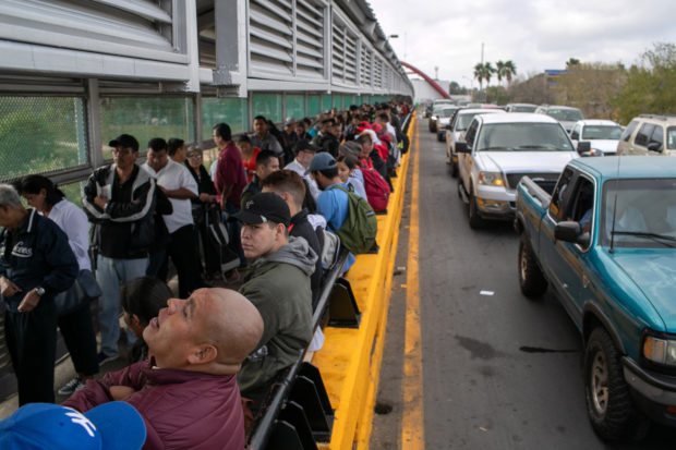 """MATAMOROS, MEXICO - DECEMBER 09: Asylum seekers (R), and Mexican citizens, (L) wait on the international bridge from Mexico to the United States on December 09, 2019 next to the border town of Matamoros, Mexico. They asylum seekers were waiting to be taken across by U.S. officials to immigration court in Brownsville, Texas. More than 1,000 Central American and Mexican asylum seekers have been staying, many for months, in a squalid camp, located next to the bridge in Matamoros, Mexico. Immigrant families seeking asylum are now required by the U.S. government to stay in Mexico as part of the Trump Administration's """"Remain in Mexico"""" process for people legally seeking political asylum in the United States. (Photo by John Moore/Getty Images)"""