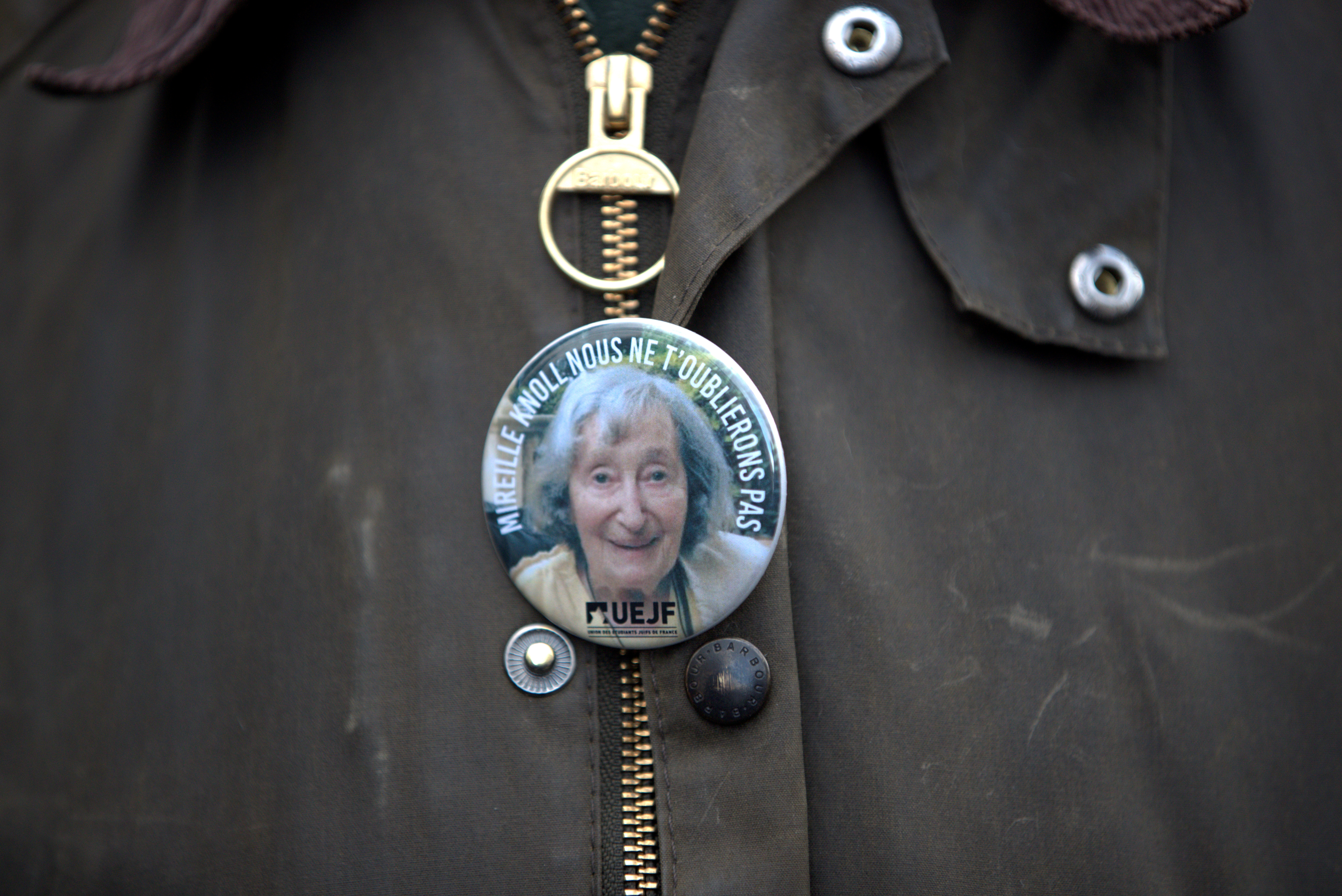 A pin with a portrait of Mireille Knoll is seen on a man's jacket during a gathering, in Paris, France, March 28, 2018. Mireille Knoll, 85, was found dead with 11 stab wounds at her apartment in a working-class district of Paris on Friday. The apartment was set ablaze after the attack and her body badly burnt. Police suspect that Knoll's Jewish religion was a motive for the killing. (REUTERS/Gonzalo Fuentes)