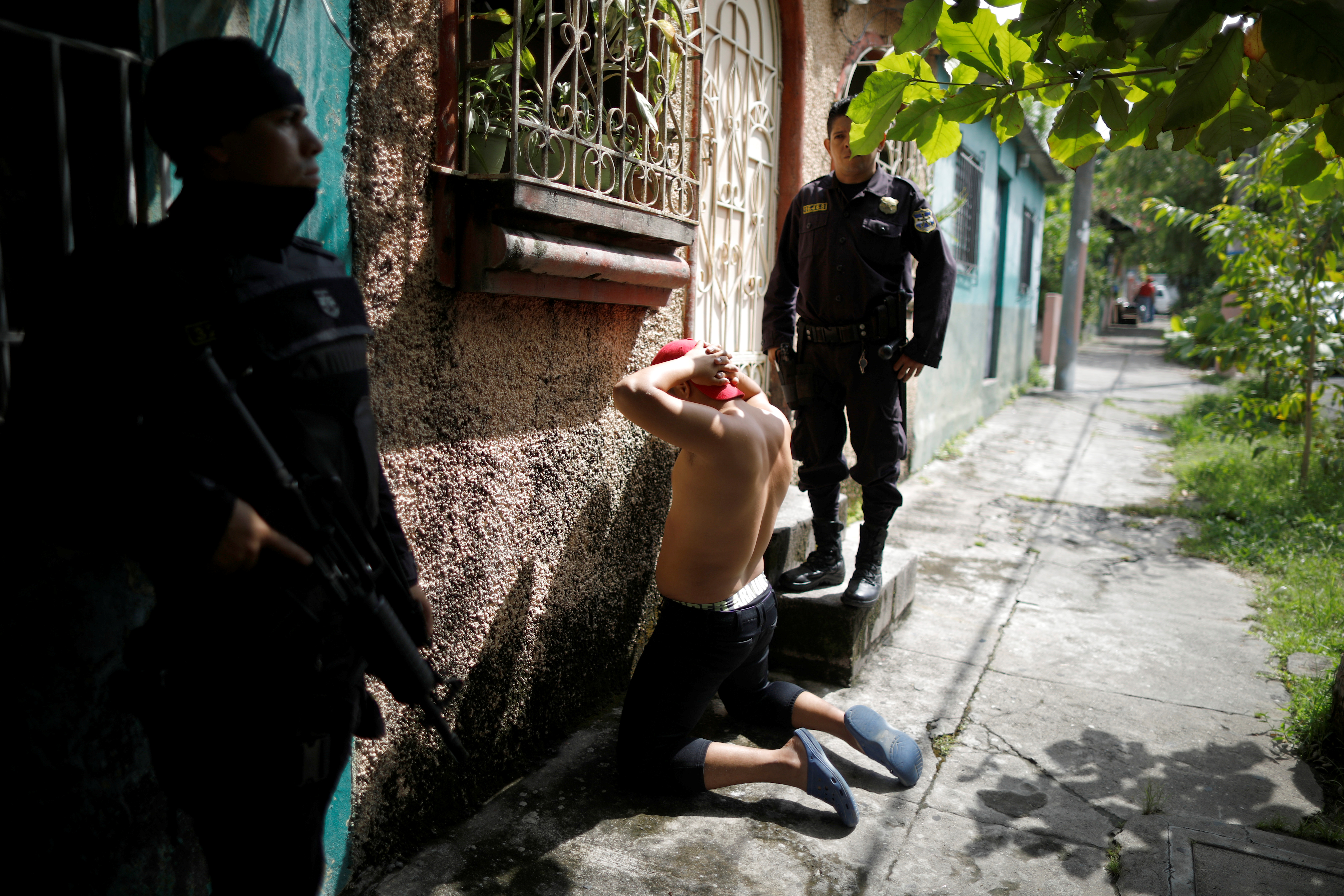 Police officers stand by a suspect outside a seized MS-13 gang usurped house during a