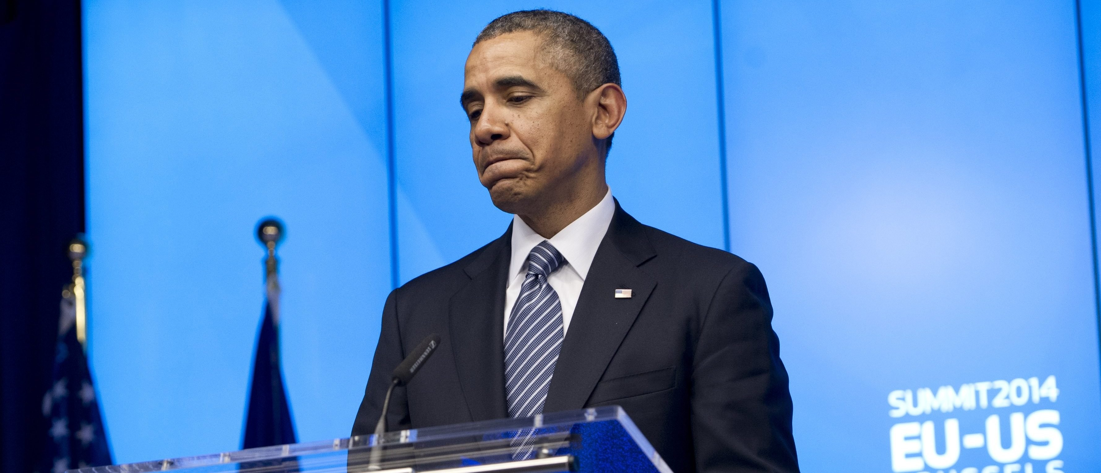 """US President Barack Obama grimaces while holding a press conference during the EU-US Summit at the European Headquarters in Brussels on March 26, 2014. Obama paid his first visit ever to the EU headquarters, cementing US-EU opposition to the takeover of Crimea after hitting out at Russian expansionism as a """"sign of weakness"""". AFP PHOTO / SAUL LOEB (Photo credit should read SAUL LOEB/AFP via Getty Images)"""