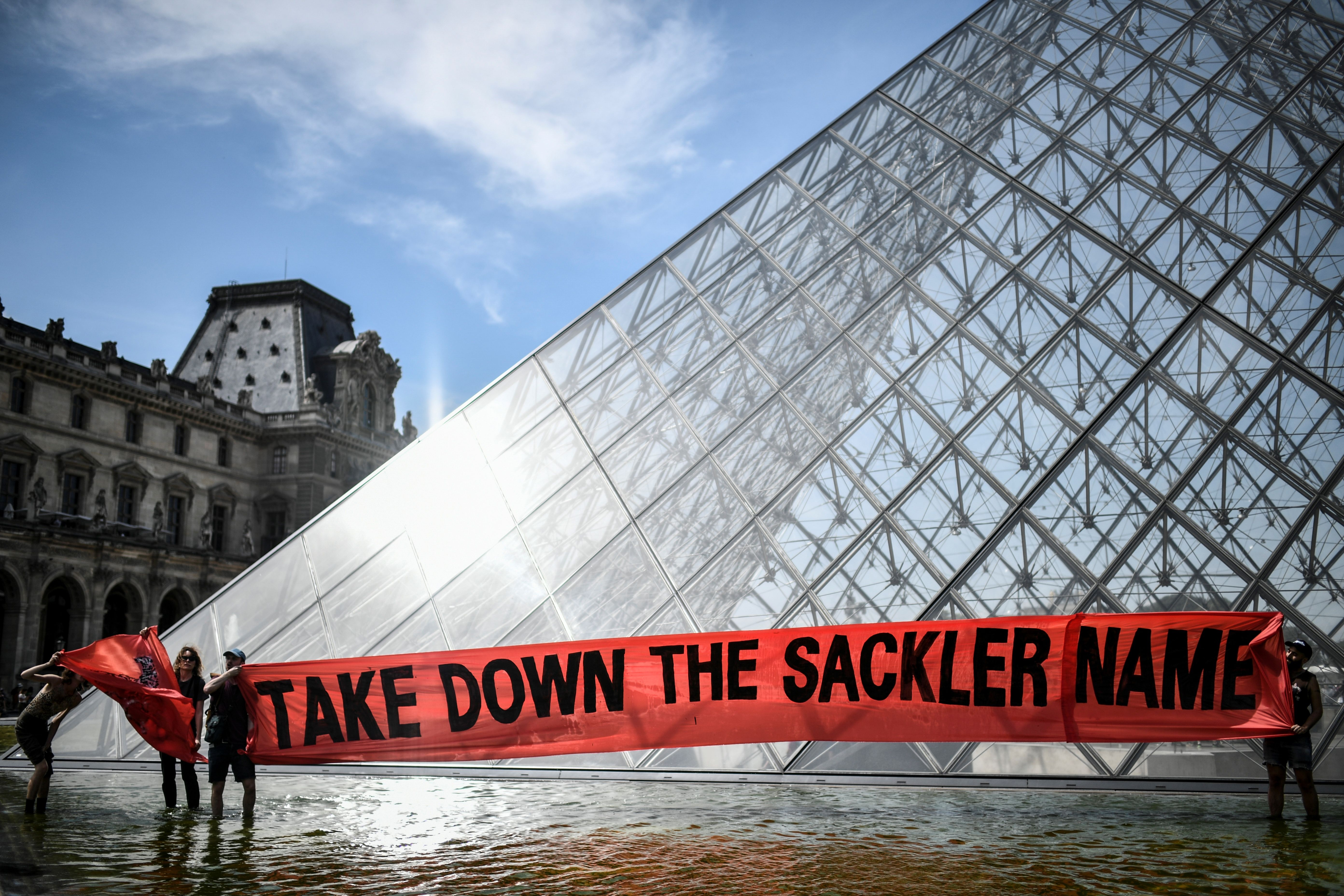 Activists protest the Sackler family in front of the Louvre on July 1, 2019. The museum's Wing of Oriental Antiquities was formerly named for the Sackler family. (Stephane De Sakutin/AFP/Getty Images)