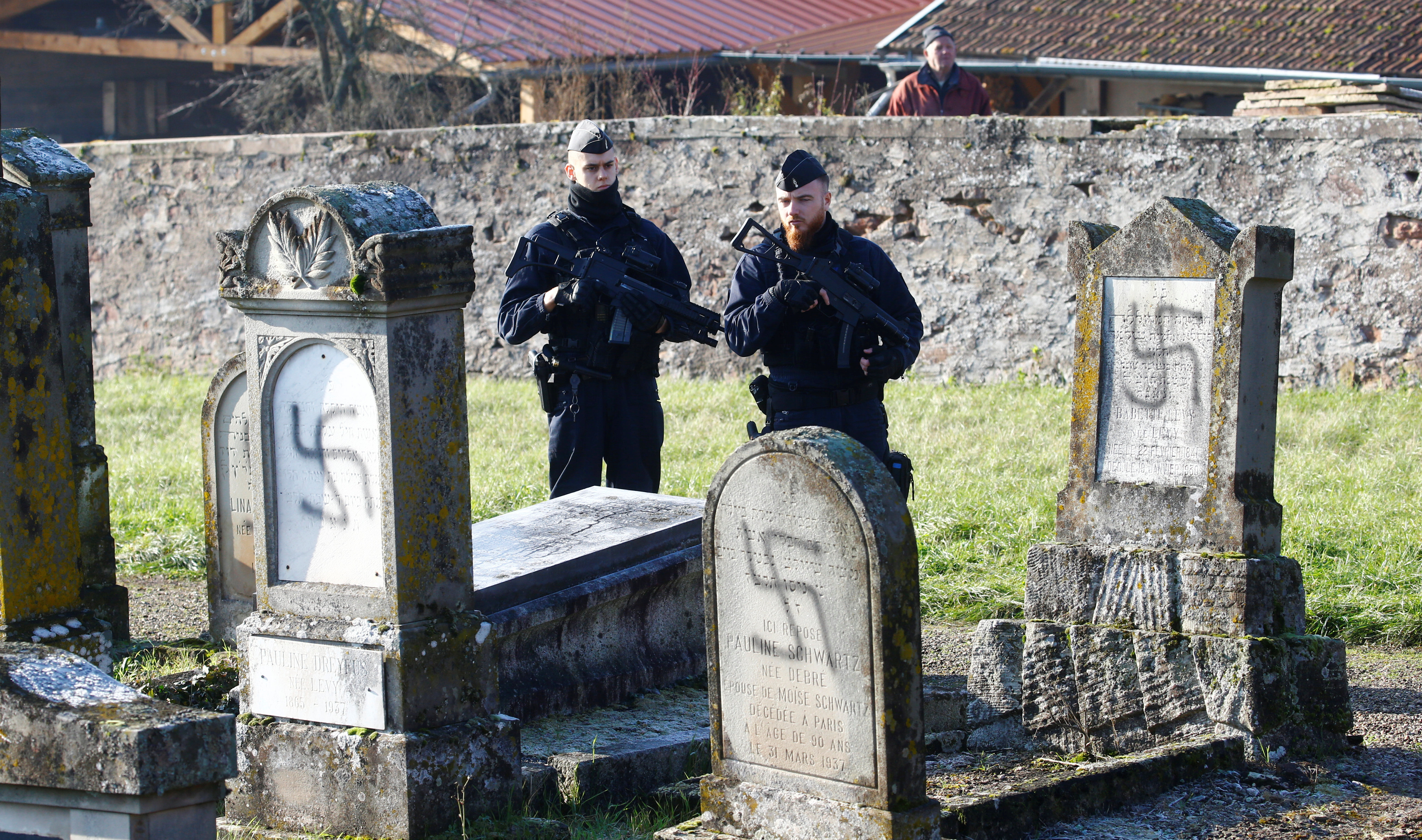 French police officers stand behind graves desecrated with swastikas at the Jewish cemetery in Westhoffen, near Strasbourg, France, December 4, 2019. (REUTERS/Arnd Wiegmann)