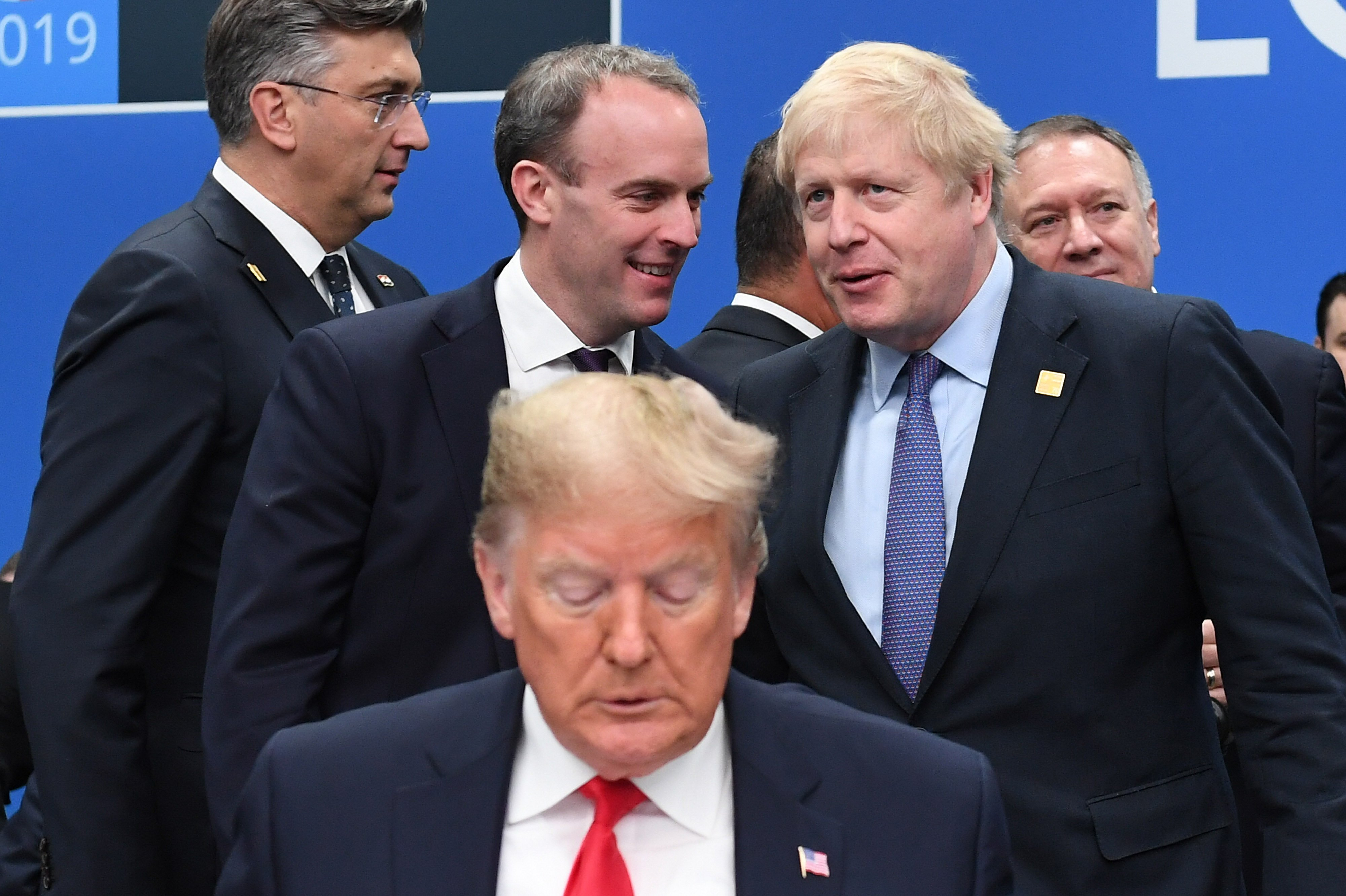 HERTFORD, ENGLAND - DECEMBER 04: US President Donald Trump (front) with Foreign Secretary Dominic Raab and British Prime Minister Boris Johnson onstage during the annual Nato heads of government summit on December 4, 2019 in Watford, England. France and the UK signed the Treaty of Dunkirk in 1947 in the aftermath of WW2 cementing a mutual alliance in the event of an attack by Germany or the Soviet Union. The Benelux countries joined the Treaty and in April 1949 expanded further to include North America and Canada followed by Portugal, Italy, Norway, Denmark and Iceland. This new military alliance became the North Atlantic Treaty Organisation (NATO). The organisation grew with Greece and Turkey becoming members and a re-armed West Germany was permitted in 1955. This encouraged the creation of the Soviet-led Warsaw Pact delineating the two sides of the Cold War. This year marks the 70th anniversary of NATO. (Photo by Stefan Rousseau - WPA Pool/Getty Images)