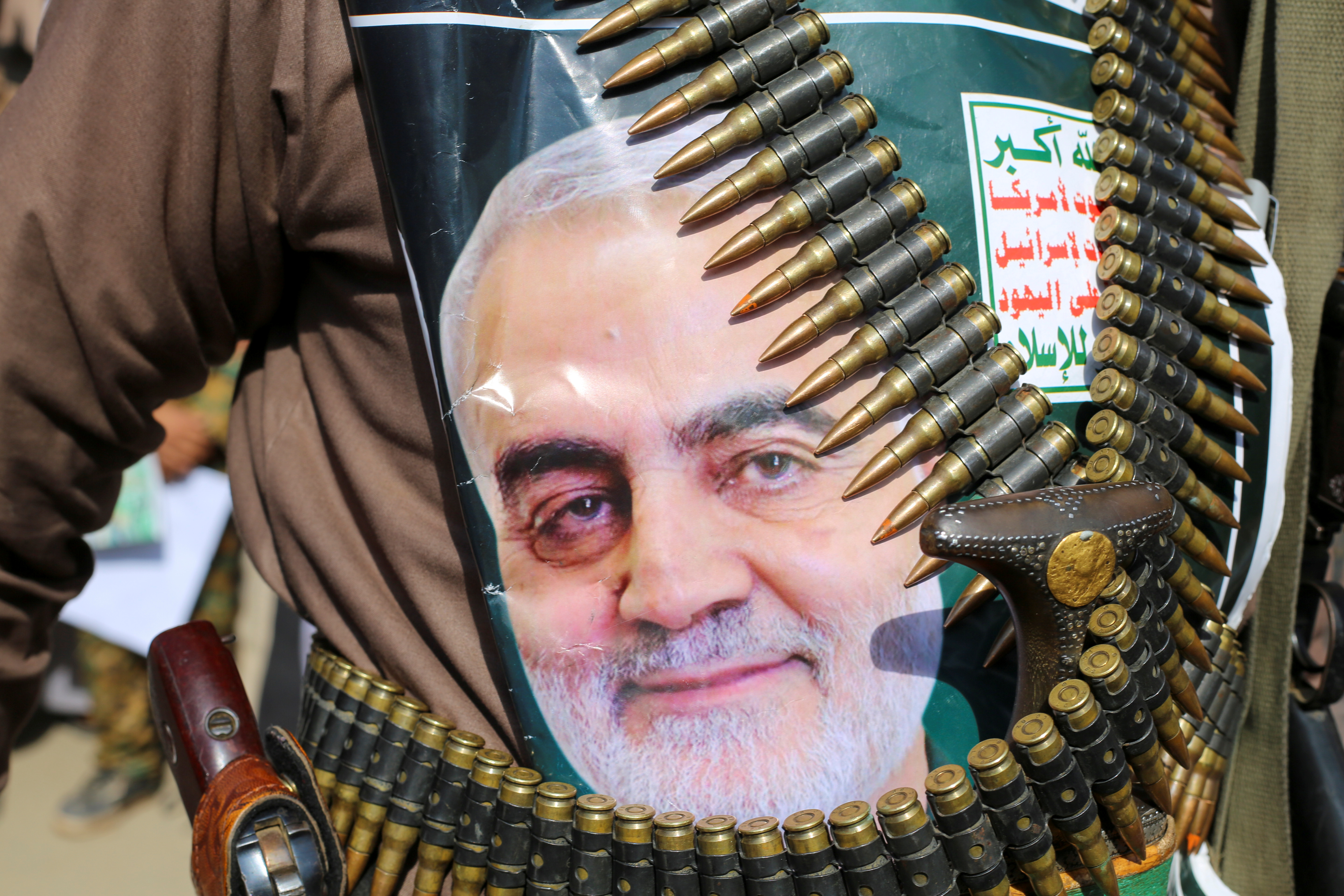 "A supporter of the Houthis has a poster attached to his waist of Iranian Major-General Qassem Soleimani, head of the elite Quds Force, who was killed in an air strike at Baghdad airport, during a rally to denounce the U.S. killing, in Saada, Yemen January 6, 2020. The writing on the poster reads: ""God is the Greatest, Death to America, Death to Israel, Curse on the Jews, Victory to Islam."" REUTERS/Naif Rahma"