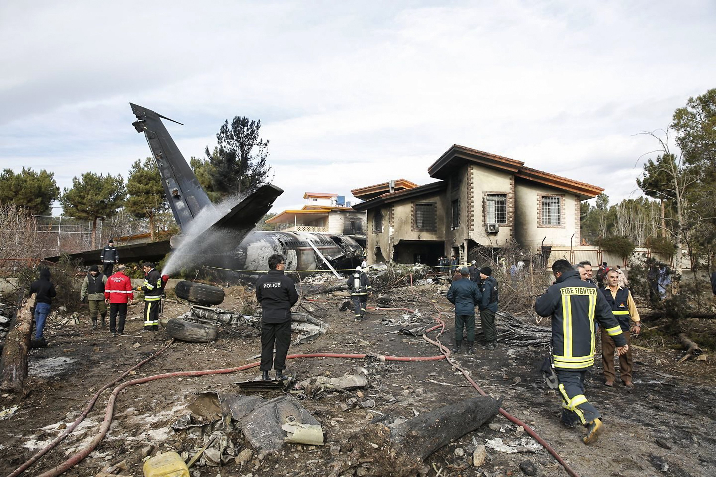 Firefighters and security forces gather amidst the debris of a Boeing 707 cargo plane that reportedly crashed into a residential complex near the Iranian capital Tehran with at least 10 people onboard on January 14, 2019. (HASAN SHIRVANI/AFP via Getty Images)