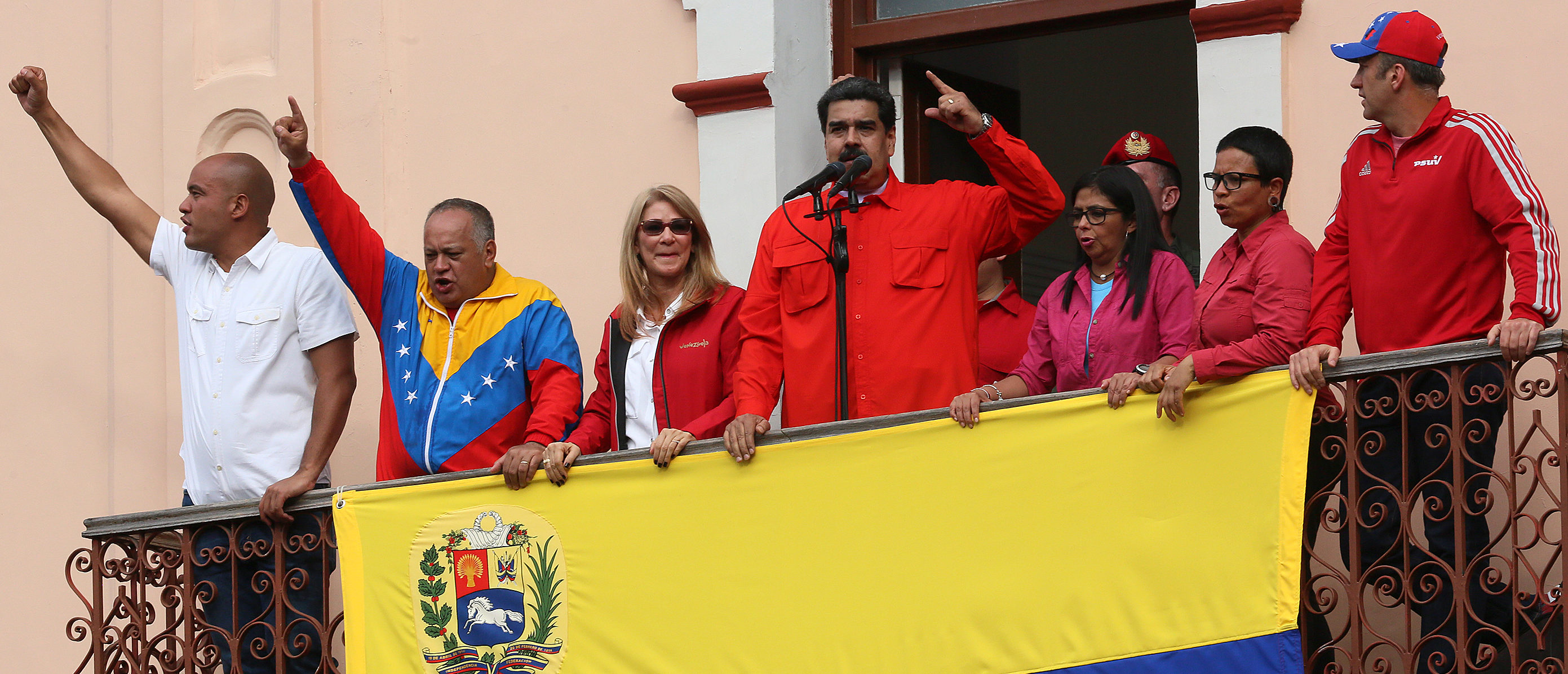 CARACAS, VENEZUELA - JANUARY 23: President of Venezuela Nicolás Maduro (C) waves a national flag as he is escorted by (FROM L TO R) Hector Rodriguez, Governor of Miranda; Diosdado Cabello, President of National Constitutional Assembly; Cilia Flores, First Lady; Excutive Vice President Delcy Rodriguez; Major Erika Farias and Economic Vice President Tareck El Aissami at the Balcón del Pueblo of the Miraflores Government Palace on January 23, 2019 in Caracas, Venezuela. Earlier today, Venezuelan opposition leader and head of the National Assembly Juan Guaido declared self interim president as was officially accepted by presidents of many countries such as US, Brazil, Chile, Canada and Argentina. Head of Supreme Justice tribunal Juan Jose Mendoza urged general attorney to act against a constitution violation. Protests continue in Caracas. (Photo by Edilzon Gamez/Getty Images)