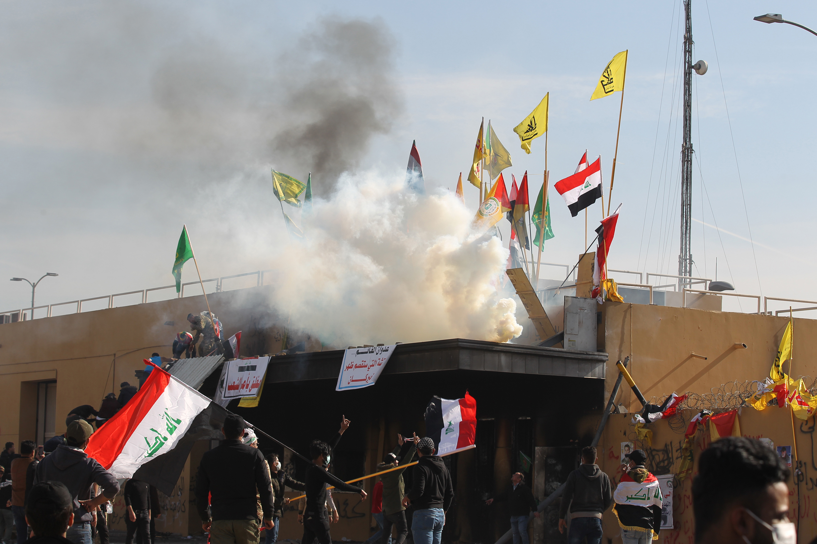 US forces (unseen) fire teargas canisters at supporters and members of the Hashed al-Shaabi paramilitary force during a demonstration outside the US embassy in the Iraqi capital Baghdad on January 1, 2020. (AHMAD AL-RUBAYE/AFP via Getty Images)
