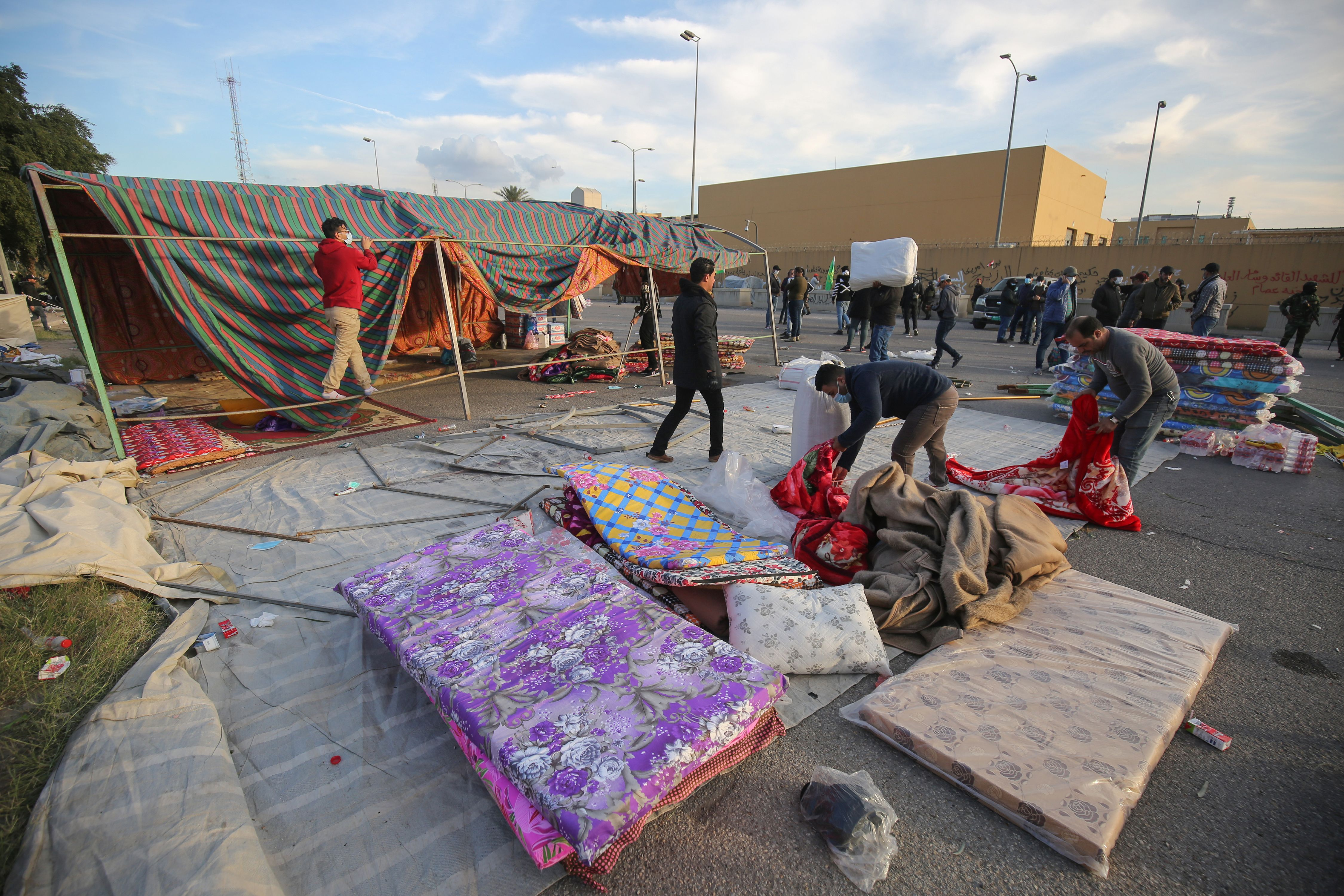 Supporters and members of Iraq's Hashed al-Shaabi paramilitary force dismantle their tents as they prepare to withdraw from the US embassy perimeter. (AHMAD AL-RUBAYE/AFP via Getty Images)