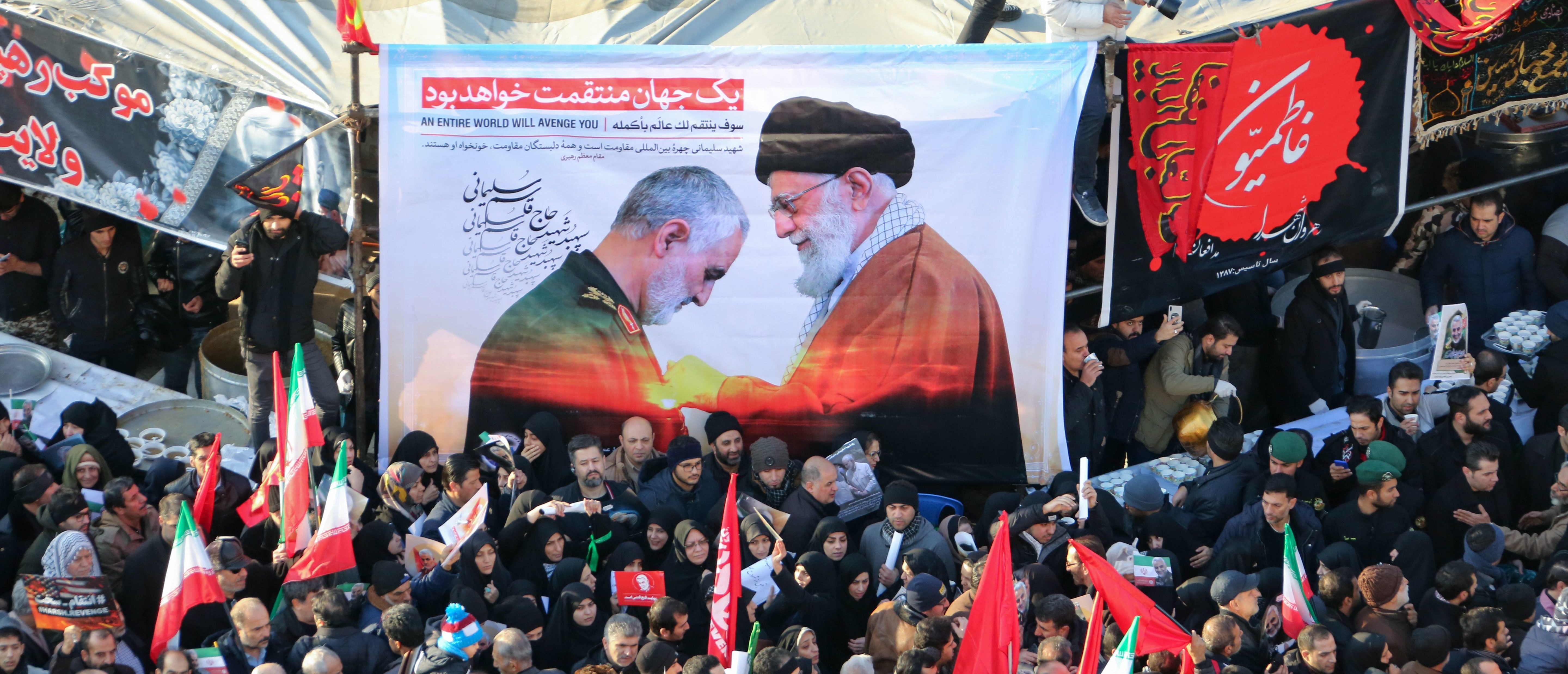 Iranian mourners carry a picture of Iran's Supreme Leader Ayatollah Ali Khamenei (R) granting the Order of Zolfaghar, the highest military honour of Iran, to General Qasem Soleimani, during the latter's funeral procession in the capital Tehran on January 6, 2020. - Downtown Tehran was brought to a standstill as mourners flooded the Iranian capital to pay an emotional homage to Soleimani, the