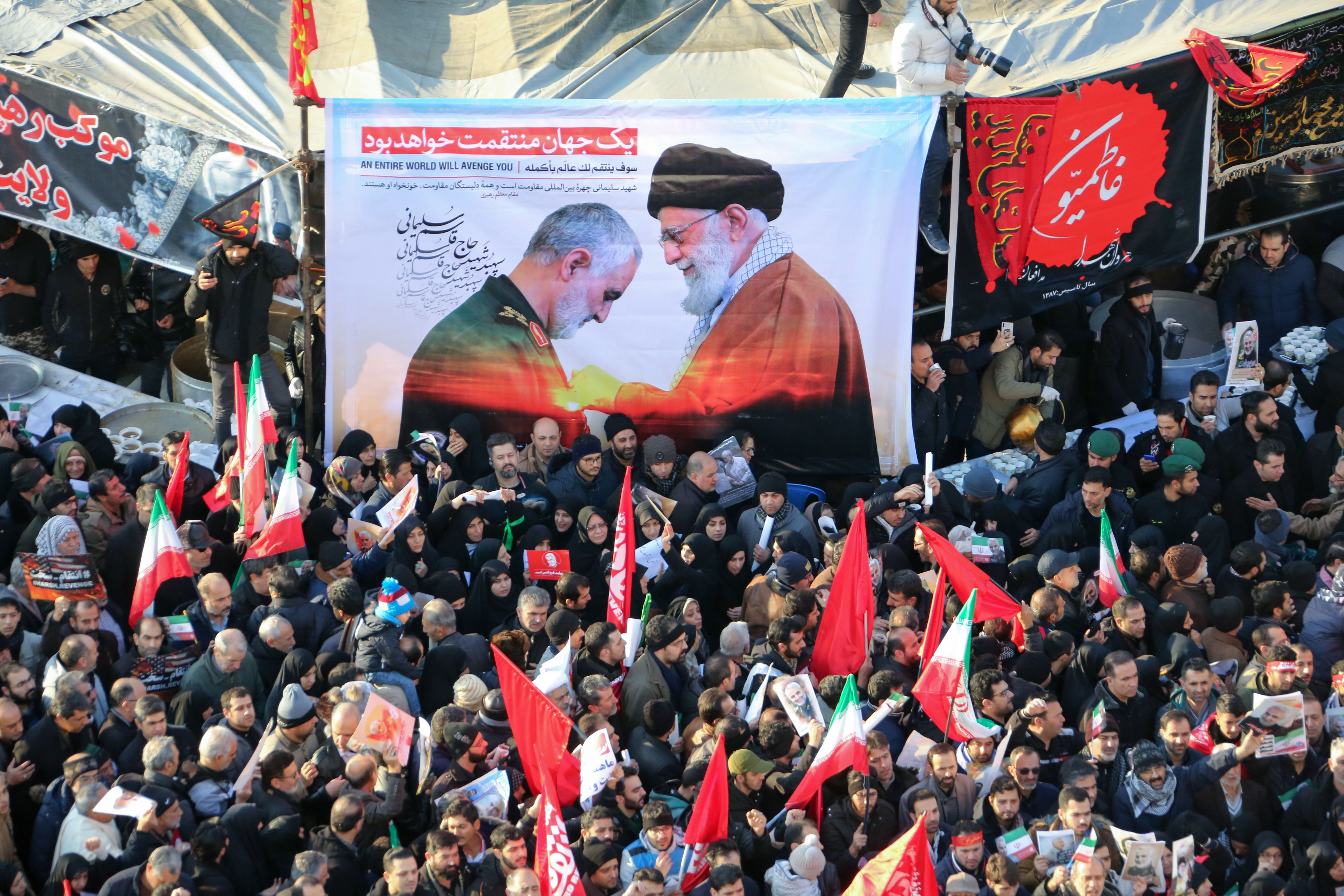 "Iranian mourners carry a picture of Iran's Supreme Leader Ayatollah Ali Khamenei (R) granting the Order of Zolfaghar, the highest military honour of Iran, to General Qasem Soleimani, during the latter's funeral procession in the capital Tehran on January 6, 2020. - Downtown Tehran was brought to a standstill as mourners flooded the Iranian capital to pay an emotional homage to Soleimani, the ""heroic"" general who spearheaded Iran's Middle East operations as commander of the Revolutionary Guards' Quds Force and was killed in a US drone strike on January 3 near Baghdad airport along with Iraqi paramilitary chief Abu Mahdi al-Muhandis and others. (Photo by ATTA KENARE/AFP via Getty Images)"