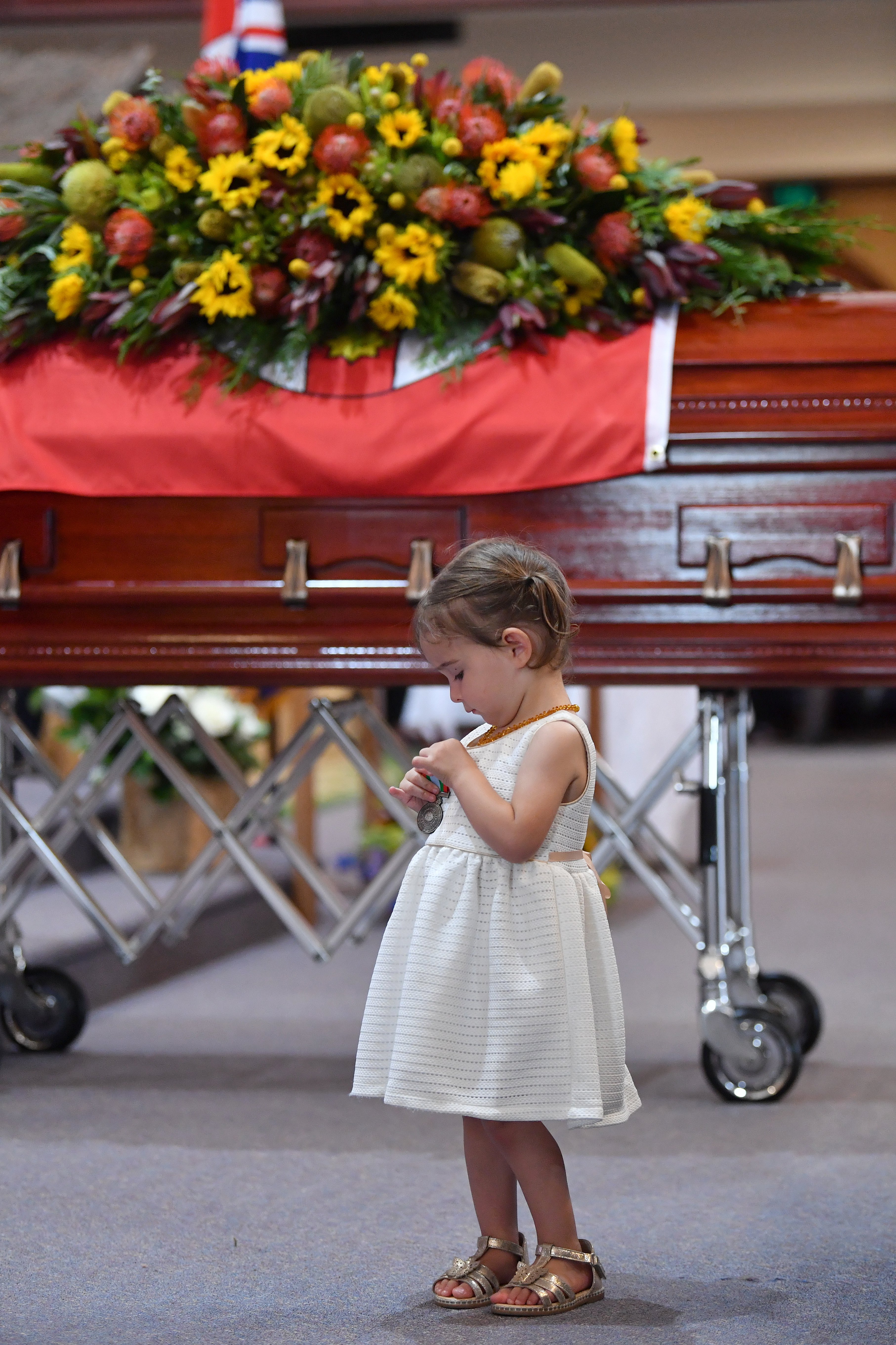 HORSLEY PARK, SYDNEY - JANUARY 07: Charlotte O'Dwyer, the young daughter of Rural Fire Service volunteer Andrew O'Dwyer stands in front of her fathers casket as she looks at the service medal presented to her by RFS Commissioner Shane Fitzsimmons during the funeral for NSW RFS volunteer Andrew O'Dwyer at Our Lady of Victories Catholic Church on January 7, 2020 in Horsley Park, Sydney. (Photo by Dean Lewins-Pool/Getty Images)