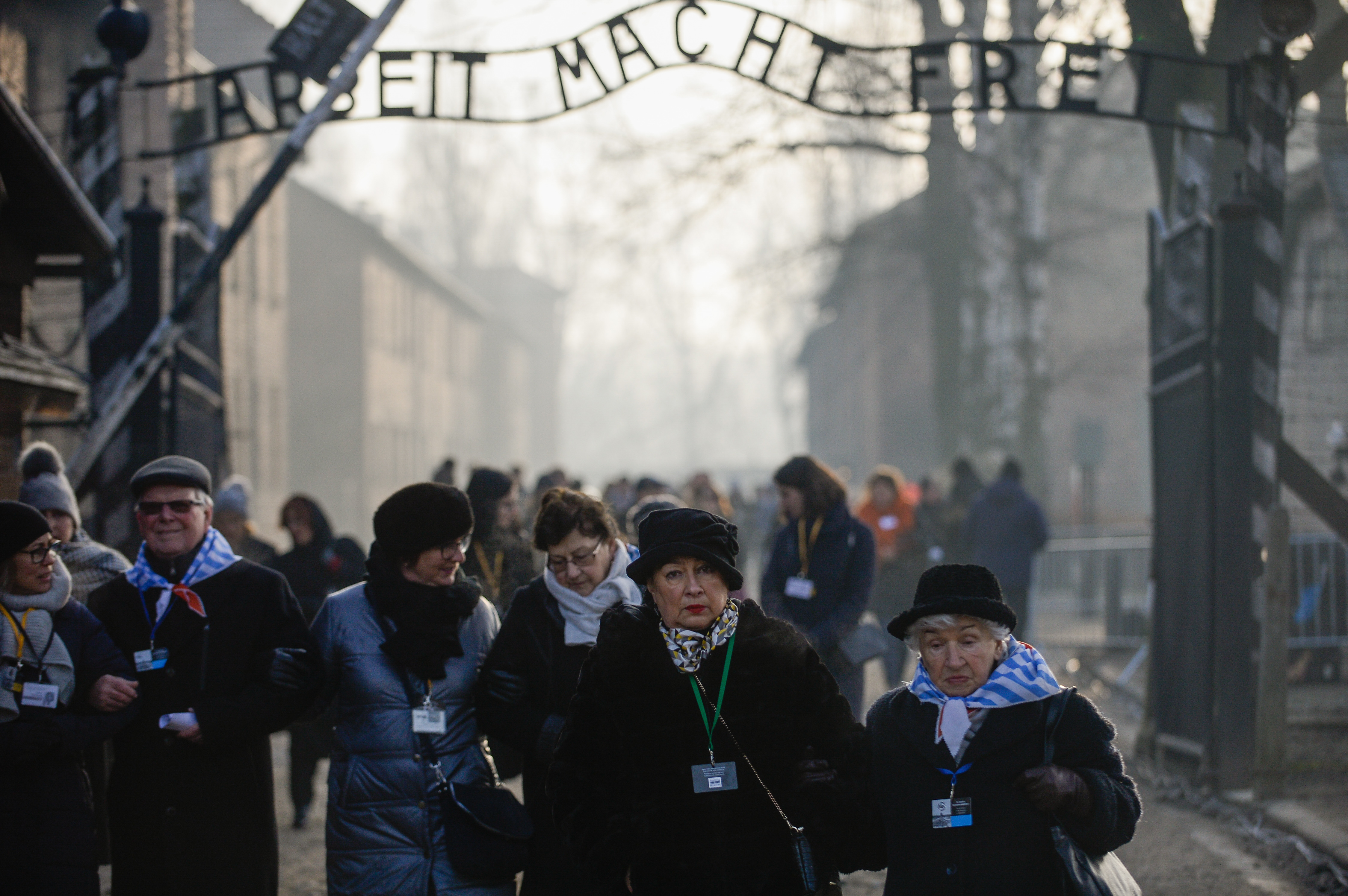 OSWIECIM, POLAND - JANUARY 27: Survivors of the Auschwitz concentration camp walk by the main gate bearing the motto Arbeit Macht Frei at the former Auschwitz I site on January 27, 2020 in Oswiecim, Poland. International leaders as well as approximately 200 survivors and their families are gathering at Auschwitz today to commemorate the 75th anniversary of the camp's liberation. The Nazis killed an estimated one million people at the camp during the World War II occupation of Poland by Nazi Germany. (Photo by Omar Marques/Getty Images)