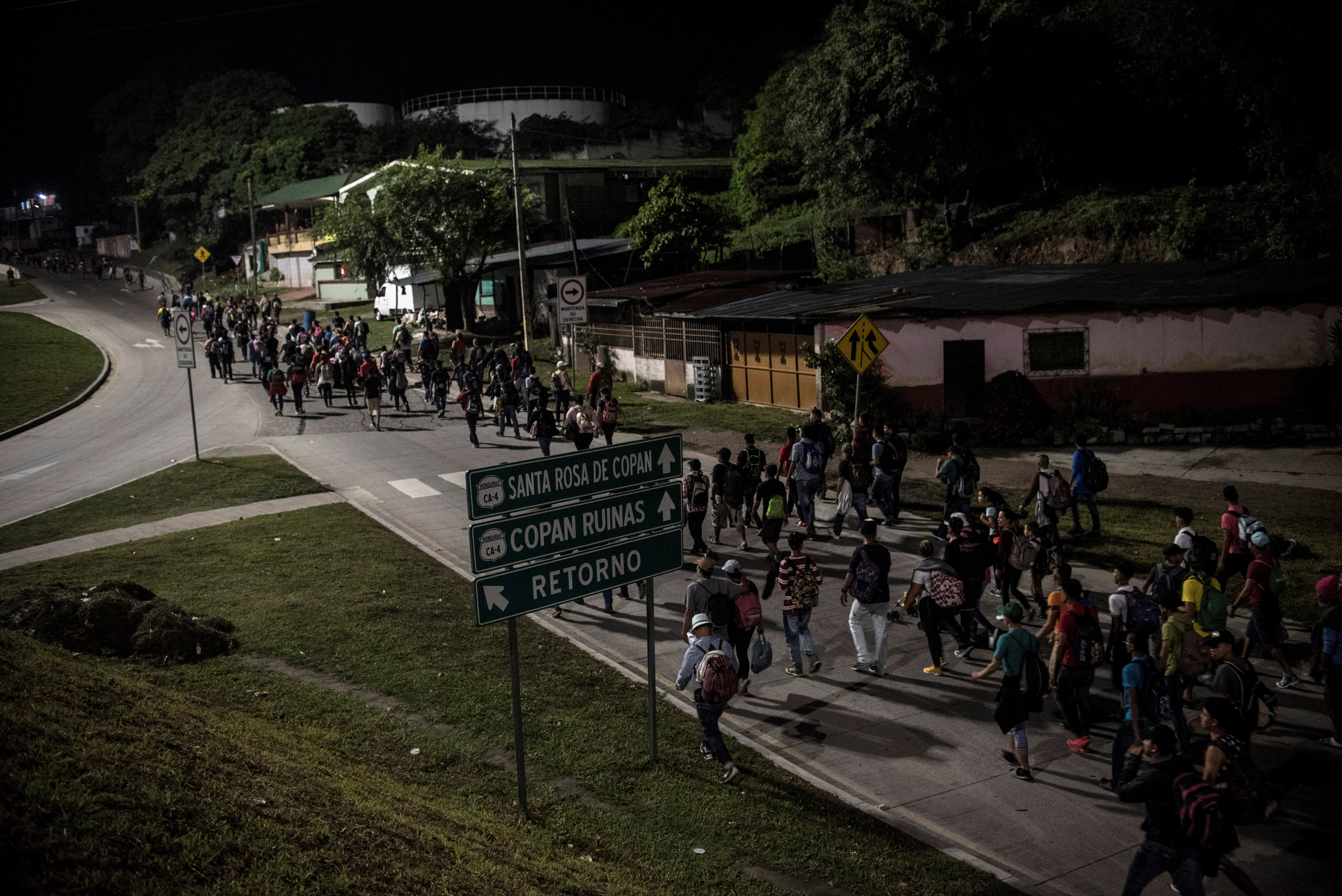 Hondurans walk along a road as they take part in a new caravan of migrants, set to head to the United States, in San Pedro Sula