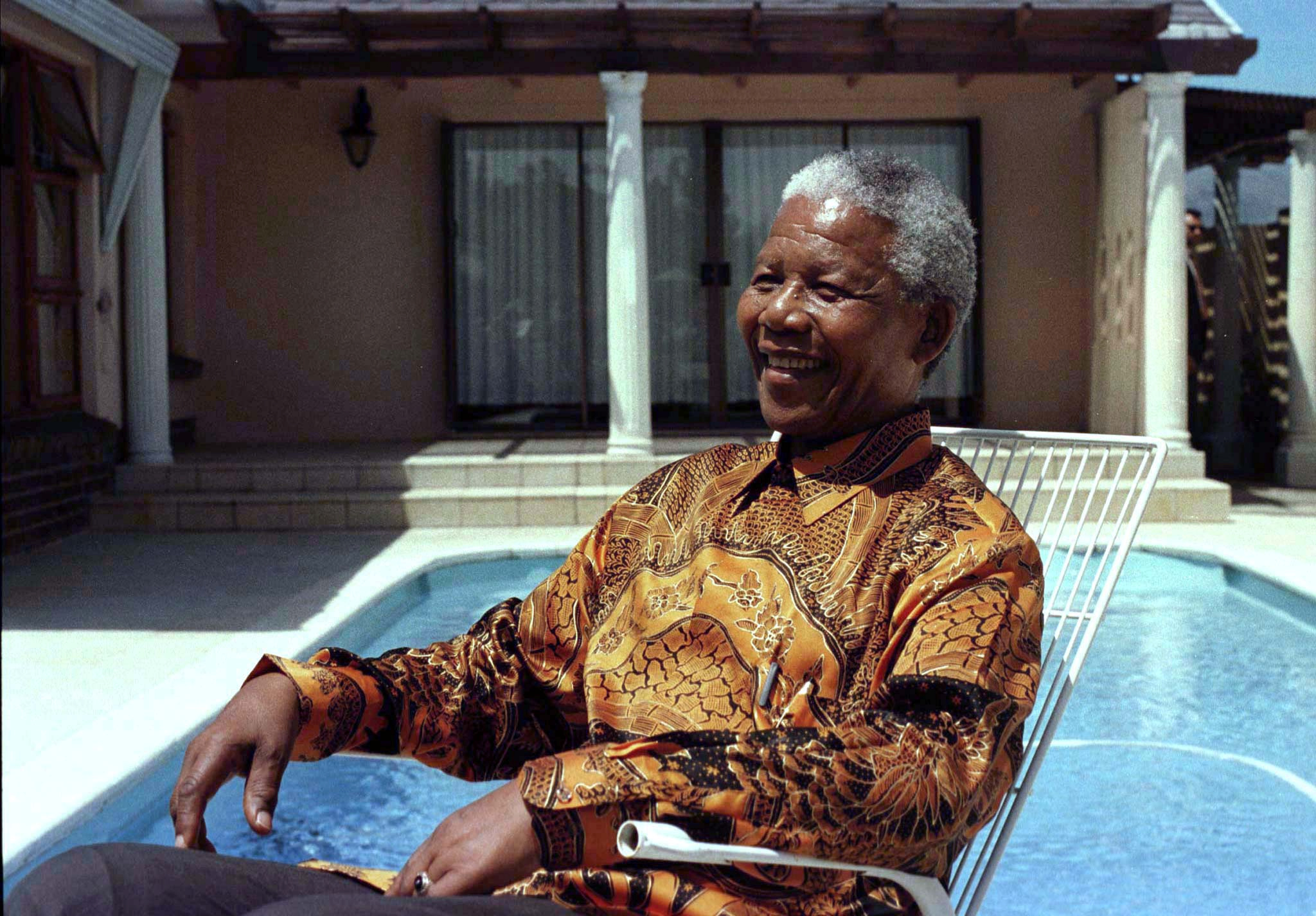 FILE PHOTO: Nelson Mandela reminisces with journalists by the pool at his former house at Victor Verster Prison in Paarl near Cape Town, South Africa, October 29, 1996. Tuesday marks the 30th aniversary of Mandela's release from the prison after serving 27 years in jail, on February 11, 1990. REUTERS/Mike Hutchings/File Photo