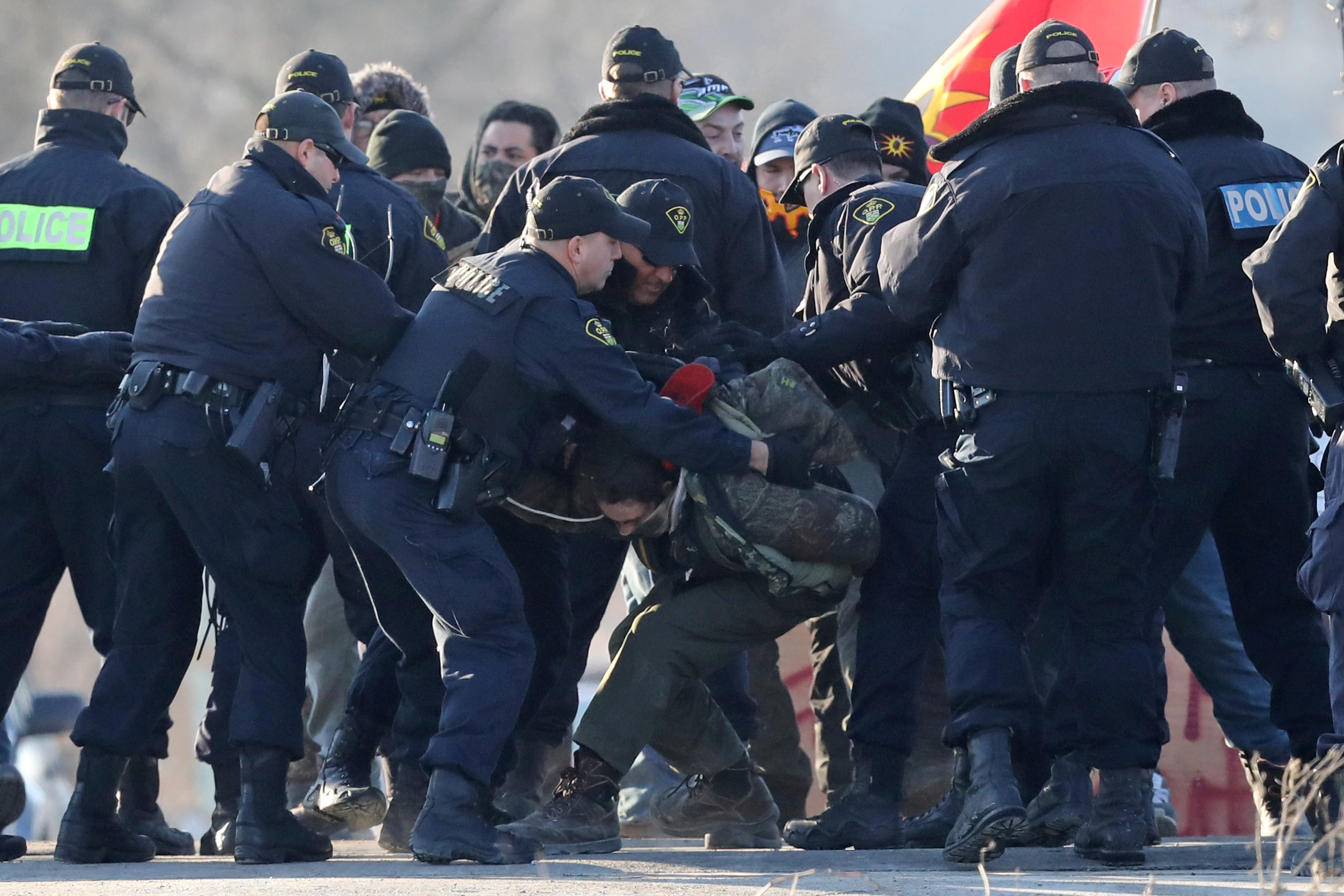Police officers make an arrest during a raid on a Tyendinaga Mohawk Territory camp next to a railway crossing in Tyendinaga, Ontario, Canada February 24, 2020. Picture taken Feb. 24, 2020. REUTERS/Chris Helgren