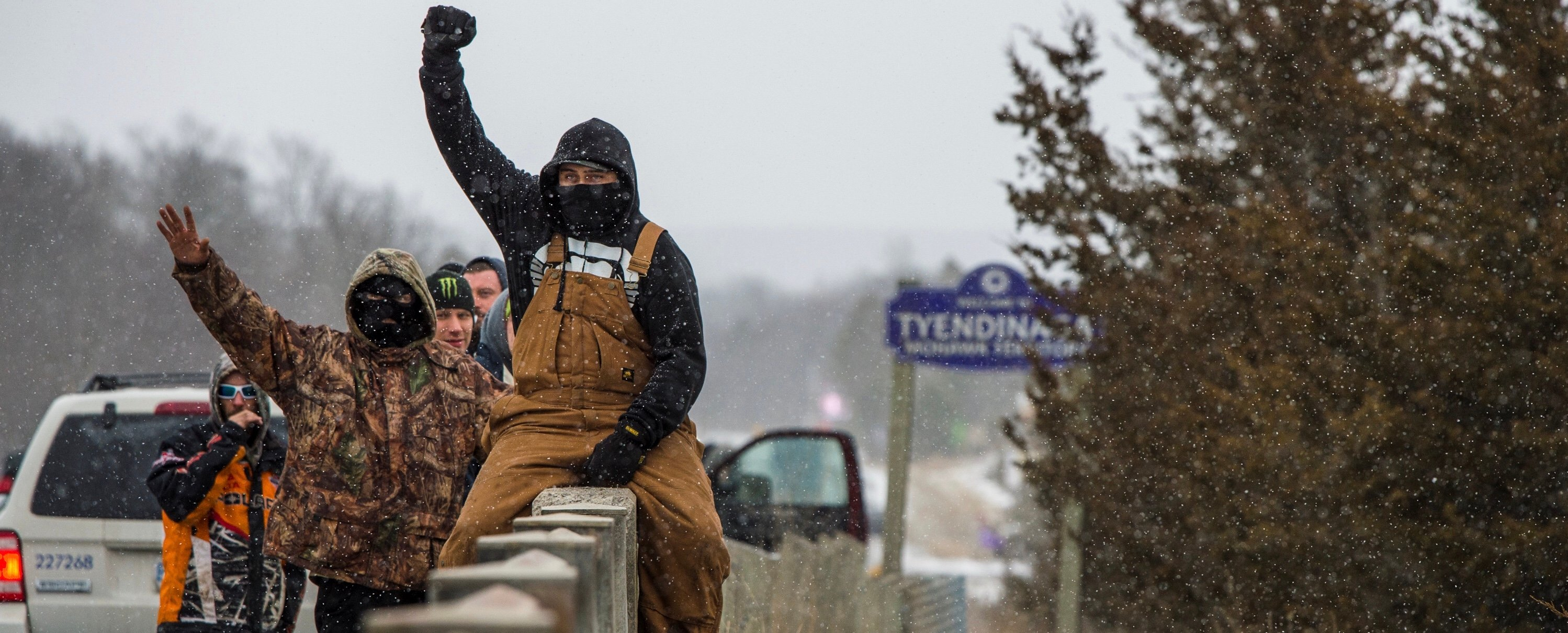 A demonstrator raises his fist as he sits on a bridge overlooking an encampment of the Tyendinaga Mohawk Territory, set up in support of the Wet'suwet'en Nation who are trying to stop construction of British Columbia's Coastal GasLink pipeline, in Tyendinaga, Ontario, Canada Feb. 26, 2020. REUTERS/Alex Filipe