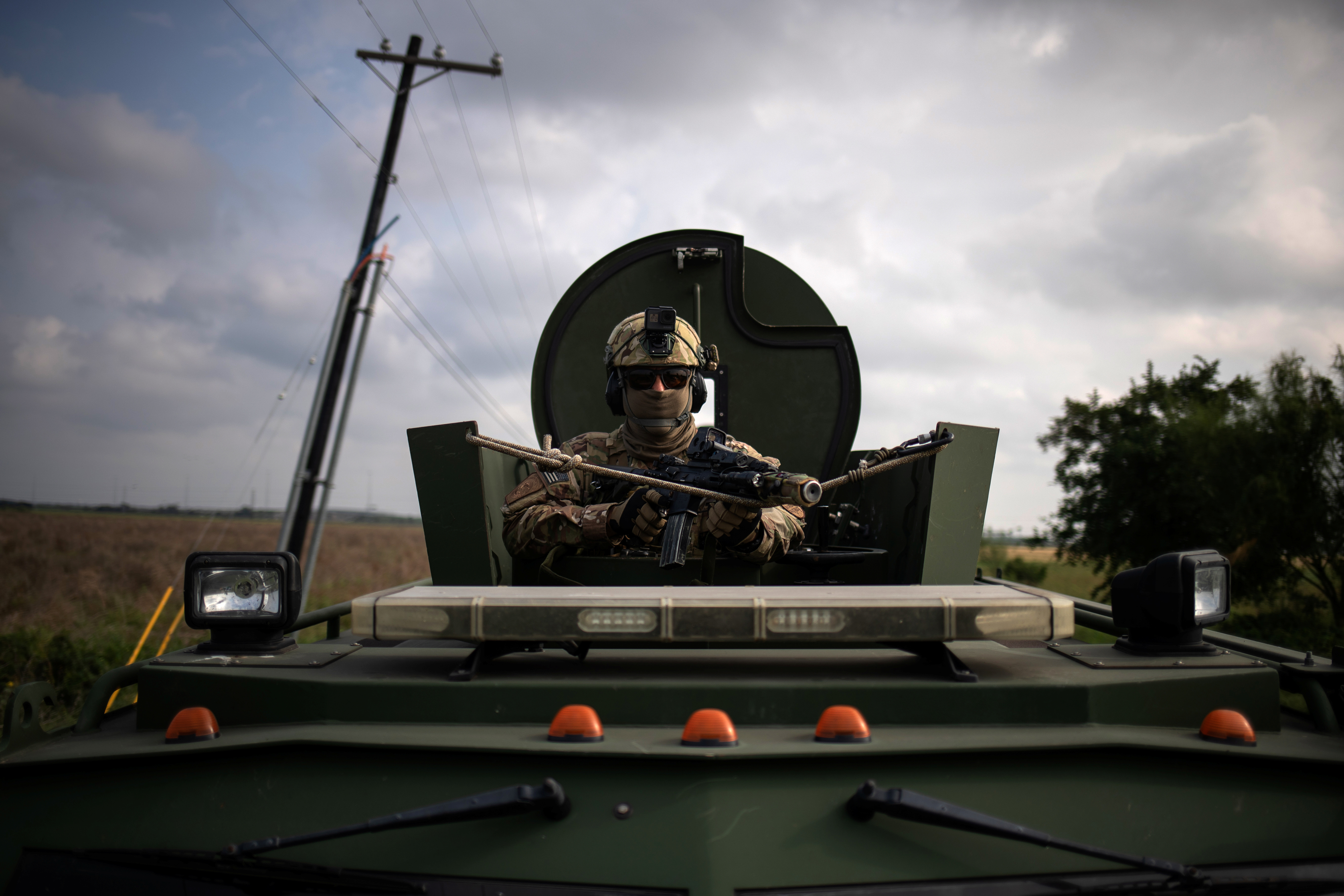 An agent with the U.S. Border Patrol Tactical Unit holds his weapon from an armored vehicle ahead of exercises in Mission, Texas