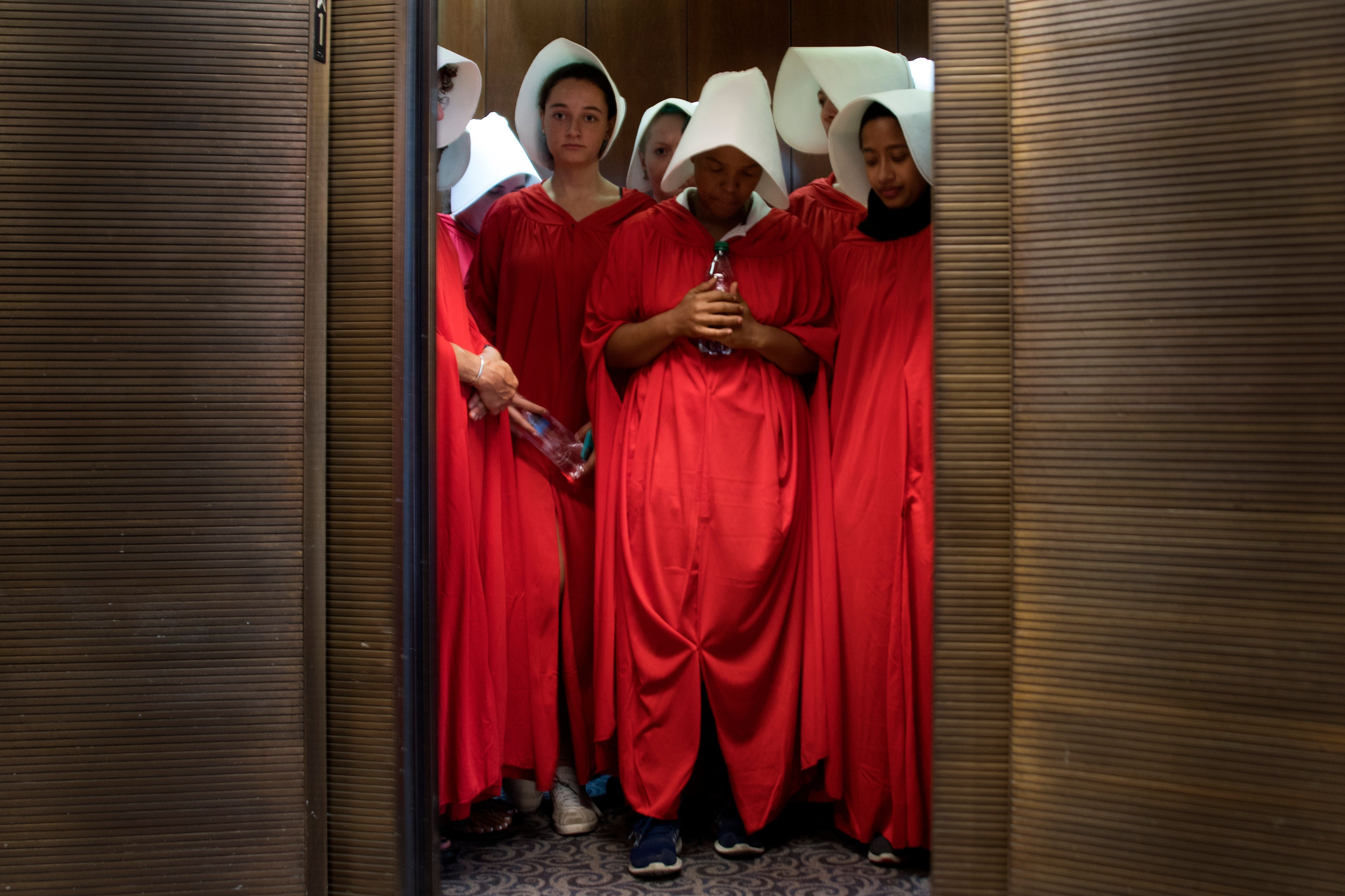 "TOPSHOT - Women dressed as characters from the novel-turned-TV series ""The Handmaid's Tale"" stand in an elevator at the Hart Senate Office Building as Supreme Court nominee Brett Kavanaugh starts the first day of his confirmation hearing in front of the US Senate on Capitol Hill in Washington DC, on September 4, 2018. - President Donald Trump's newest Supreme Court nominee Brett Kavanaugh is expected to face punishing questioning from Democrats this week over his endorsement of presidential immunity and his opposition to abortion. Some two dozen witnesses are lined up to argue for and against confirming Kavanaugh, who could swing the nine-member high court decidedly in conservatives' favor for years to come. Democrats have mobilized heavily to prevent his approval. (Photo by Jim WATSON / AFP) (Photo by JIM WATSON/AFP via Getty Images)"