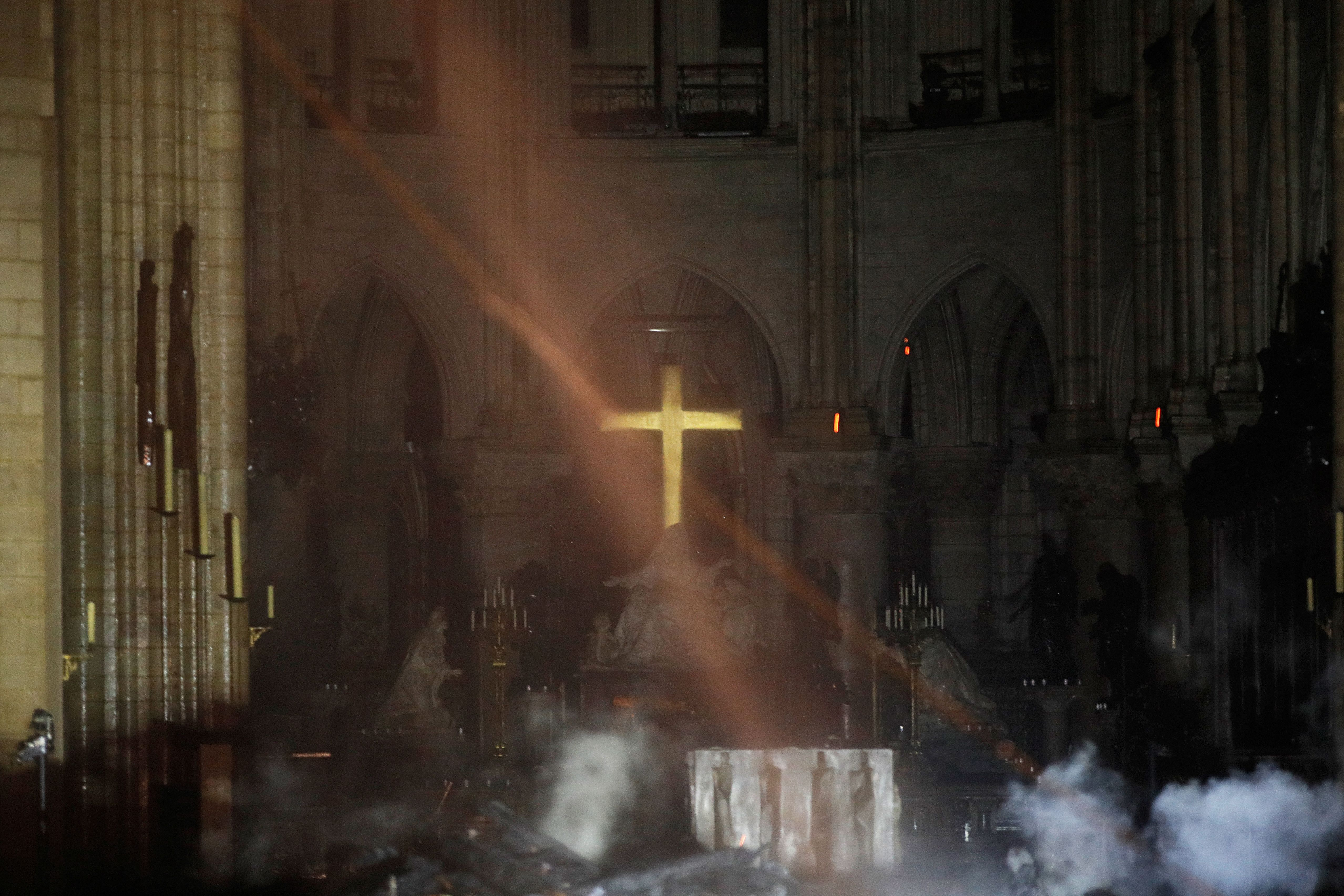 TOPSHOT - Smoke rises around the alter in front of the cross inside the Notre-Dame Cathedral as the fire continues to burn on April 16, 2019 in the French capital Paris. - A huge fire swept through the roof of the famed Notre-Dame Cathedral in central Paris on April 15, 2019, sending flames and huge clouds of grey smoke billowing into the sky. The flames and smoke plumed from the spire and roof of the gothic cathedral, visited by millions of people a year. A spokesman for the cathedral told AFP that the wooden structure supporting the roof was being gutted by the blaze. (Photo by PHILIPPE WOJAZER / POOL / AFP) (Photo credit should read PHILIPPE WOJAZER/AFP via Getty Images)