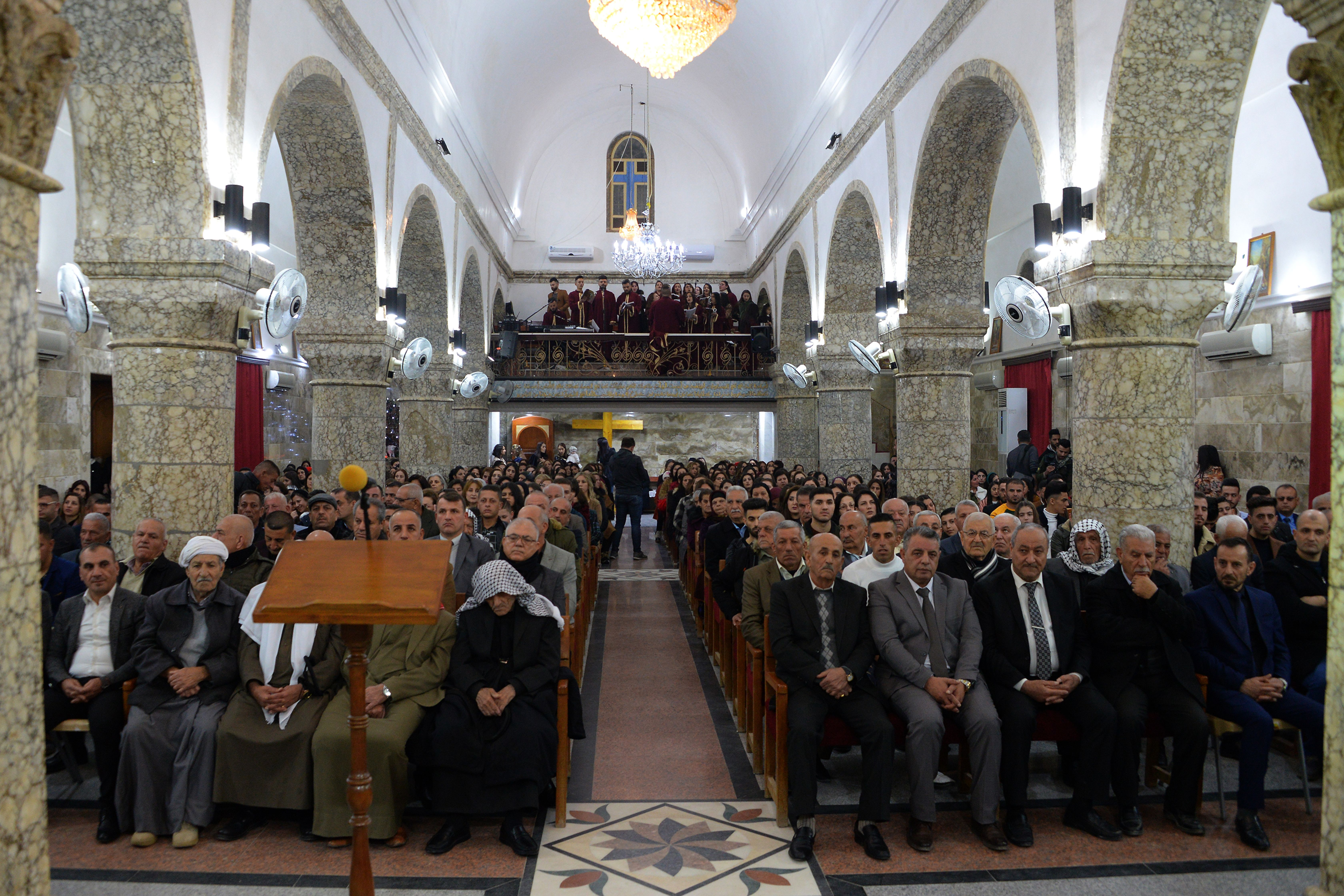 Iraqi Christians attend Christmas eve mass at the Syriac Catholic Church of Mar Jacob al-Muqataa in the predominantly Iraqi Christian town of Qaraqosh, in Niniveh province (Photo by ZAID AL-OBEIDI/AFP via Getty Images)