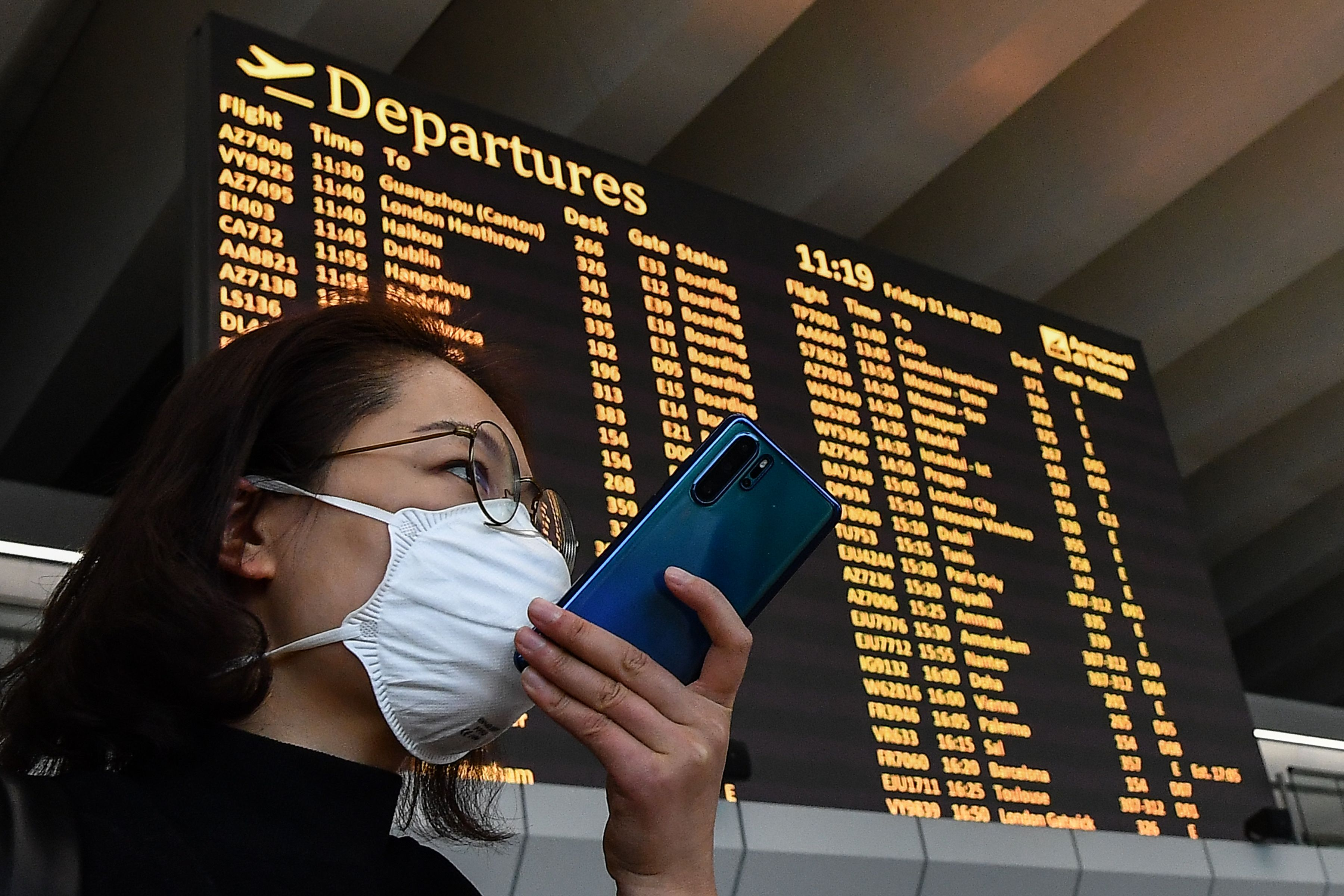 A passenger wearing a respiratory mask speaks on her smartphone by the departures board on January 31, 2020 at Rome's Fiumicino airport, as a number of airlines halted or reduced flights to China as the country struggles to contain the spread of the deadly novel coronavirus. - The Italian government said on January 30, 2020 it was suspending all flights between Italy and China, adding it was the first EU government to do so. China has advised its citizens to postpone trips abroad and cancelled overseas group tours, while several countries have urged their citizens to avoid travel to China. (Photo by Tiziana FABI / AFP) (Photo by TIZIANA FABI/AFP via Getty Images)