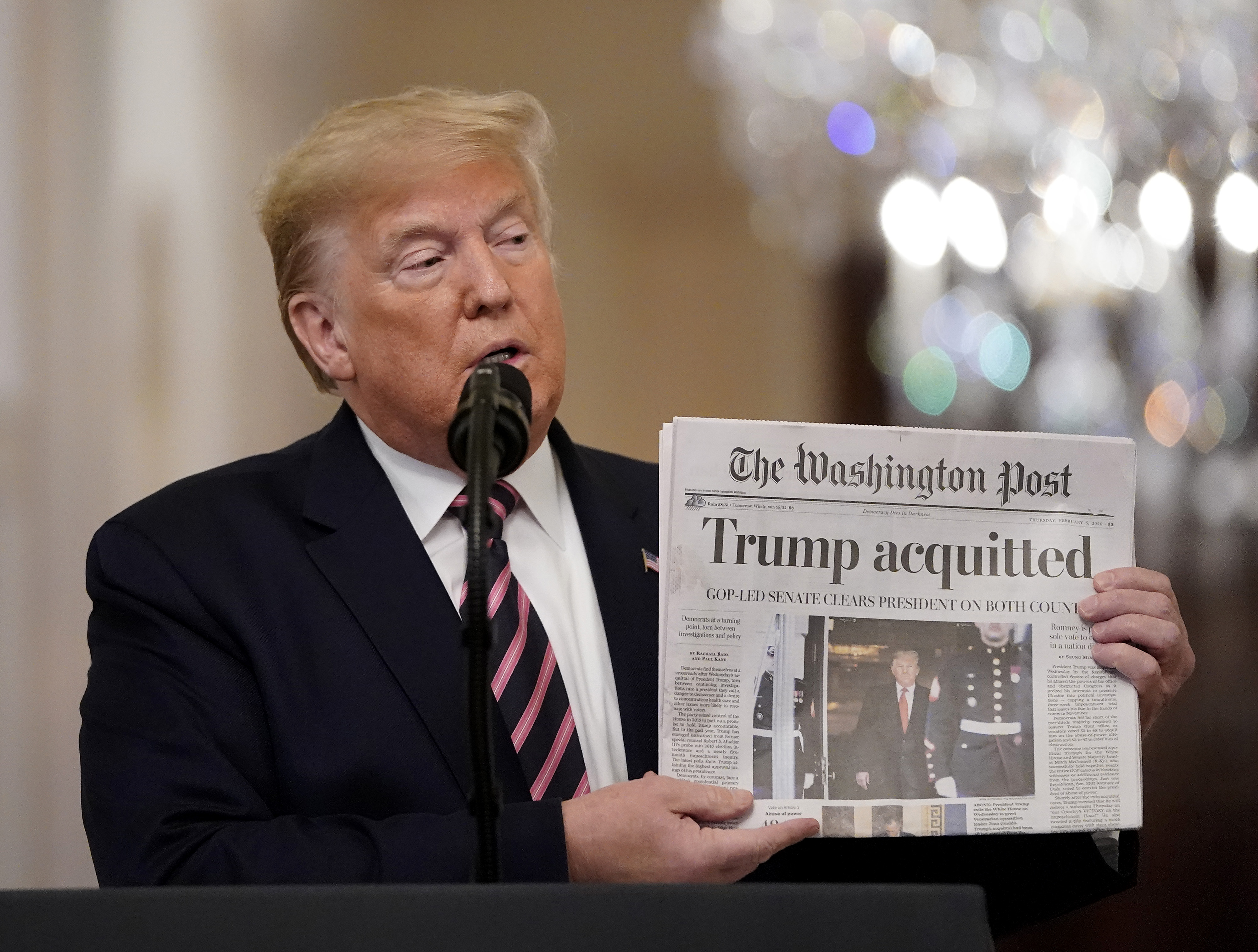 WASHINGTON, DC - FEBRUARY 06: U.S. President Donald Trump holds a copy of The Washington Post as he speaks in the East Room of the White House one day after the U.S. Senate acquitted on two articles of impeachment, ion February 6, 2020 in Washington, DC. After five months of congressional hearings and investigations about President Trump's dealings with Ukraine, the U.S. Senate formally acquitted the president on Wednesday of charges that he abused his power and obstructed Congress. (Photo by Drew Angerer/Getty Images)